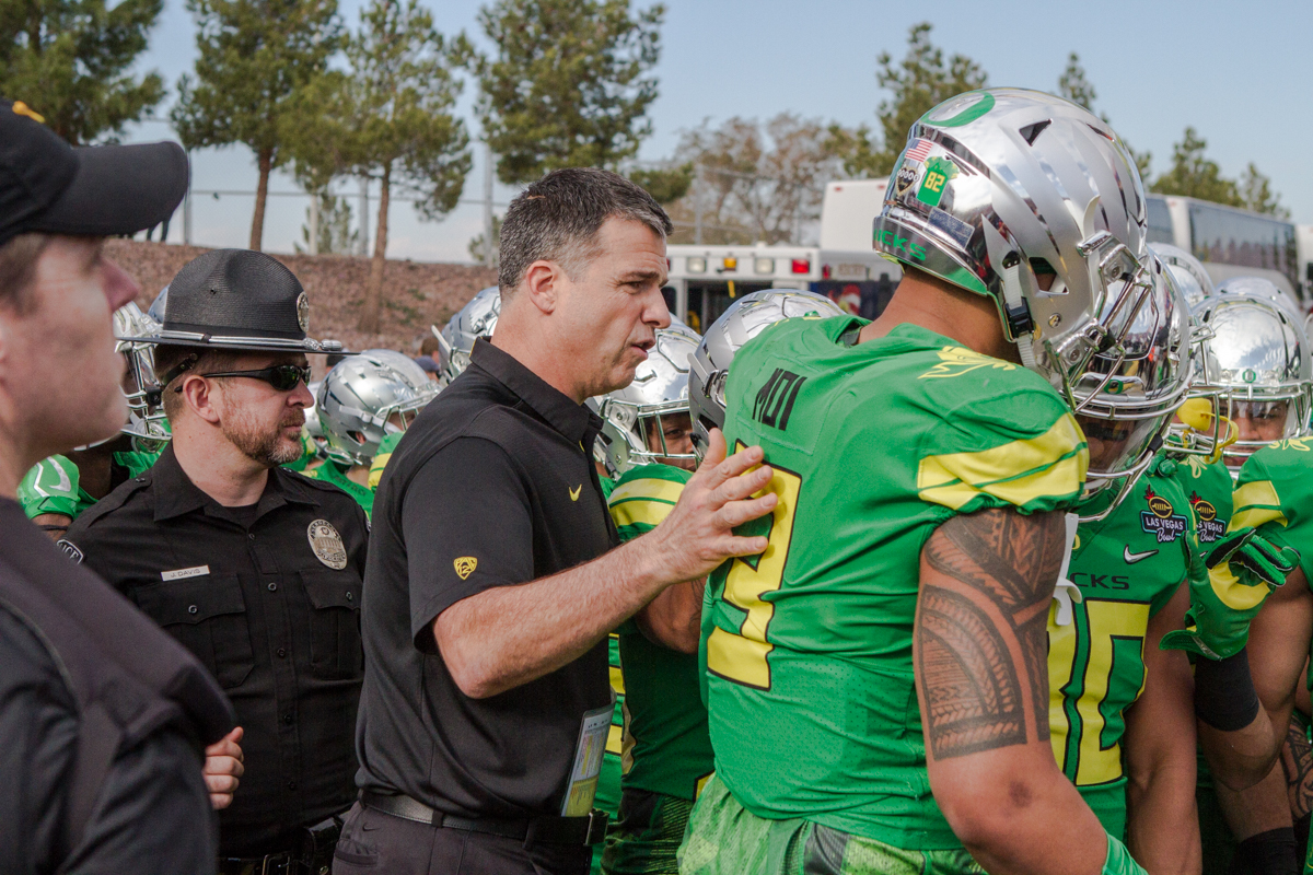 New Oregon Head Coach Mario Cristobal talks with players before kickoff. The Oregon Ducks trail the Boise State Broncos 14 to 24 at the end of the first half of the Las Vegas Bowl at Sam Boyd Stadium in Las Vegas, Nevada. Photo by Ben Lonergan, Oregon News Lab