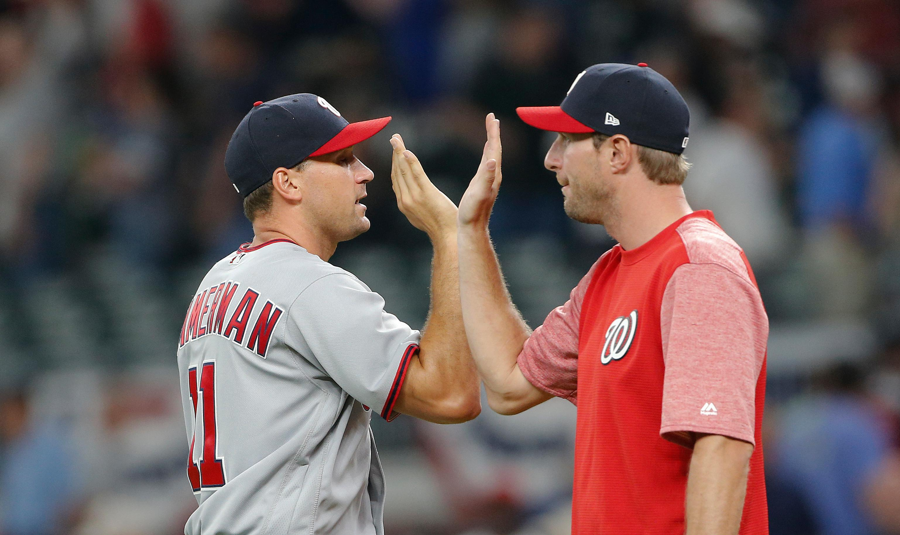Washington Nationals first baseman Ryan Zimmerman (11), left, celebrates with pitcher Max Scherzer (31) after the Nationals defeated the Atlanta Braves 3-2 in a baseball game Thursday, April 20, 2017, in Atlanta. Zimmerman hit a two-run home. Scherzer did not play. (AP Photo/John Bazemore)