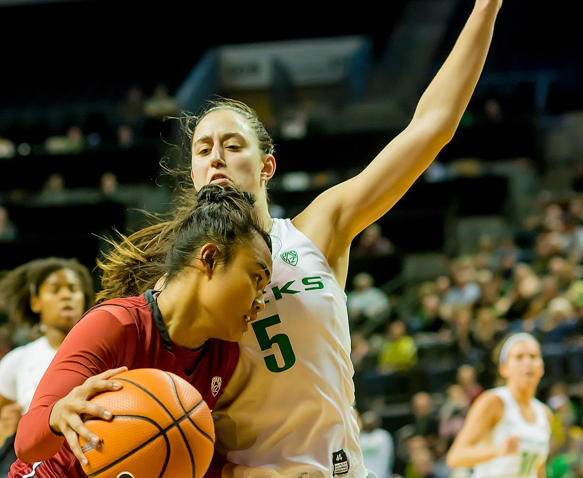 Oregon Ducks Maite Casoria (#5) attempts to block the forward progress of the University of Washington Cougars Chanelle Molina (#11). In their first conference basketball game of the season, the Oregon Women Ducks defeated the Washington State Cougars 89-56 in Matt Knight Arena Saturday afternoon. Oregon's Ruthy Hebard ran up 25 points with 10 rebounds. Sabrina Ionescu shot 25 points with five three-pointers and three rebounds. Lexi Bando added 18 points, with four three-pointers and pulled down three rebounds. Satou Sabally ended the game with 14 points with one three-pointer and two rebounds. The Ducks are now 12-2 overall with 1-0 in conference and the Cougars stand at 7-6 overall and 0-1 in conference play. The Oregon Women Ducks next play the University of Washington Huskies at 1:00 pm on Sunday. Photo by Karly DeWees, Oregon News Lab