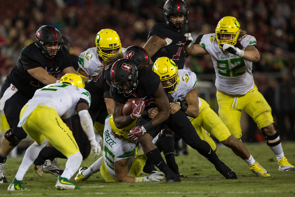Stanford runningback Trevor Speights (#23) runs the ball through a trio of Oregon defenders.  The Oregon Ducks fell to the Stanford Cardinal 49-7 at Stanford Stadium, bringing their record to 4-3 for the season.  Photo by Austin Hicks, Oregon News Lab