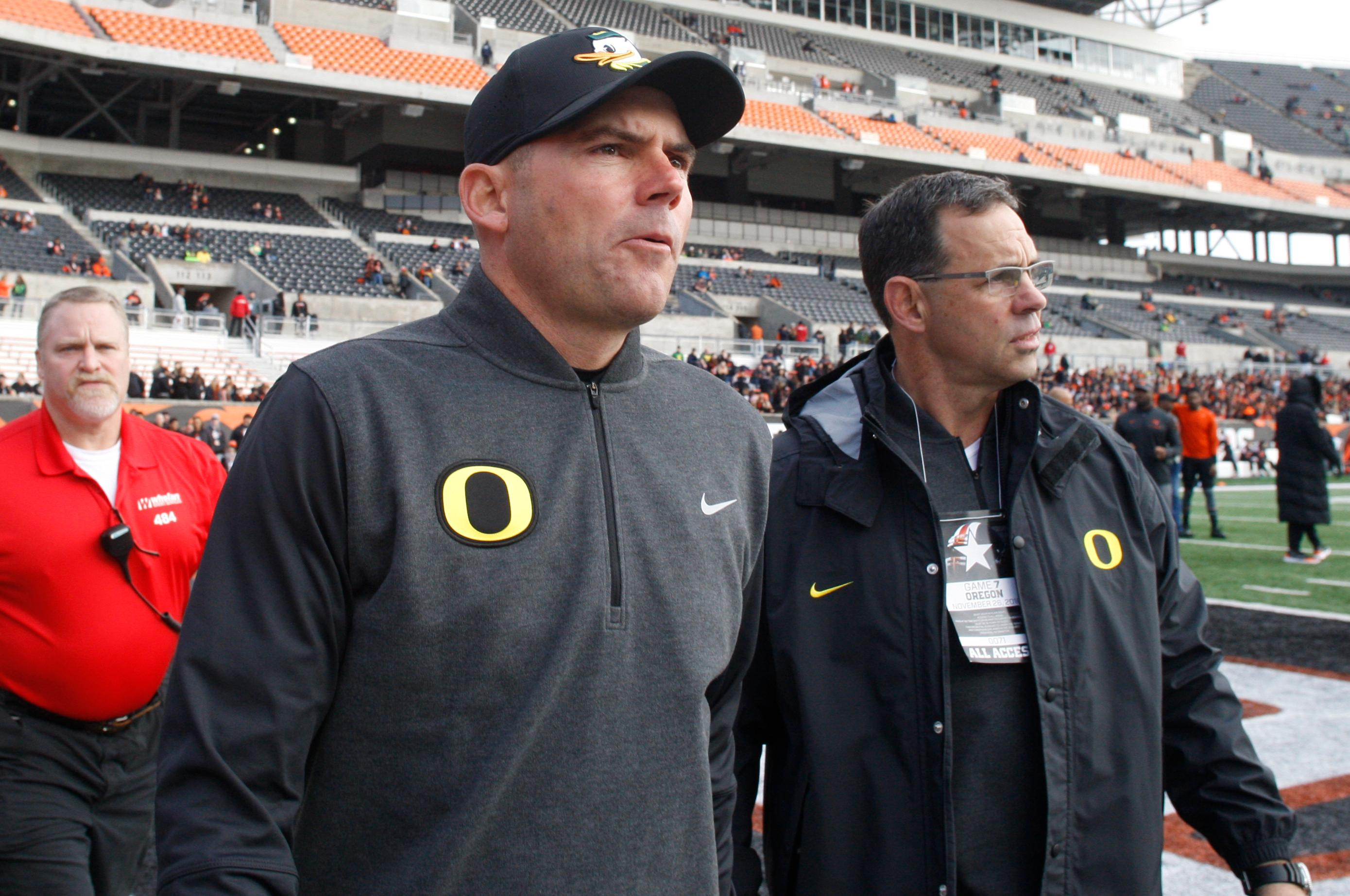 FILE - In this Nov. 26, 2016, file photo, then-Oregon head coach Mark Helfrich, center, comes onto the field for an interview before an NCAA college football game against Oregon State, in Corvallis, Ore. The Chicago Bears have hired former Oregon coach Mark Helfrich as their offensive co-ordinator. The Bears also announced Friday, Jan. 12, 2018, that Chris Tabor will become special teams co-ordinator and Charles London will take over as running backs coach. (AP Photo/Timothy J. Gonzalez, File)
