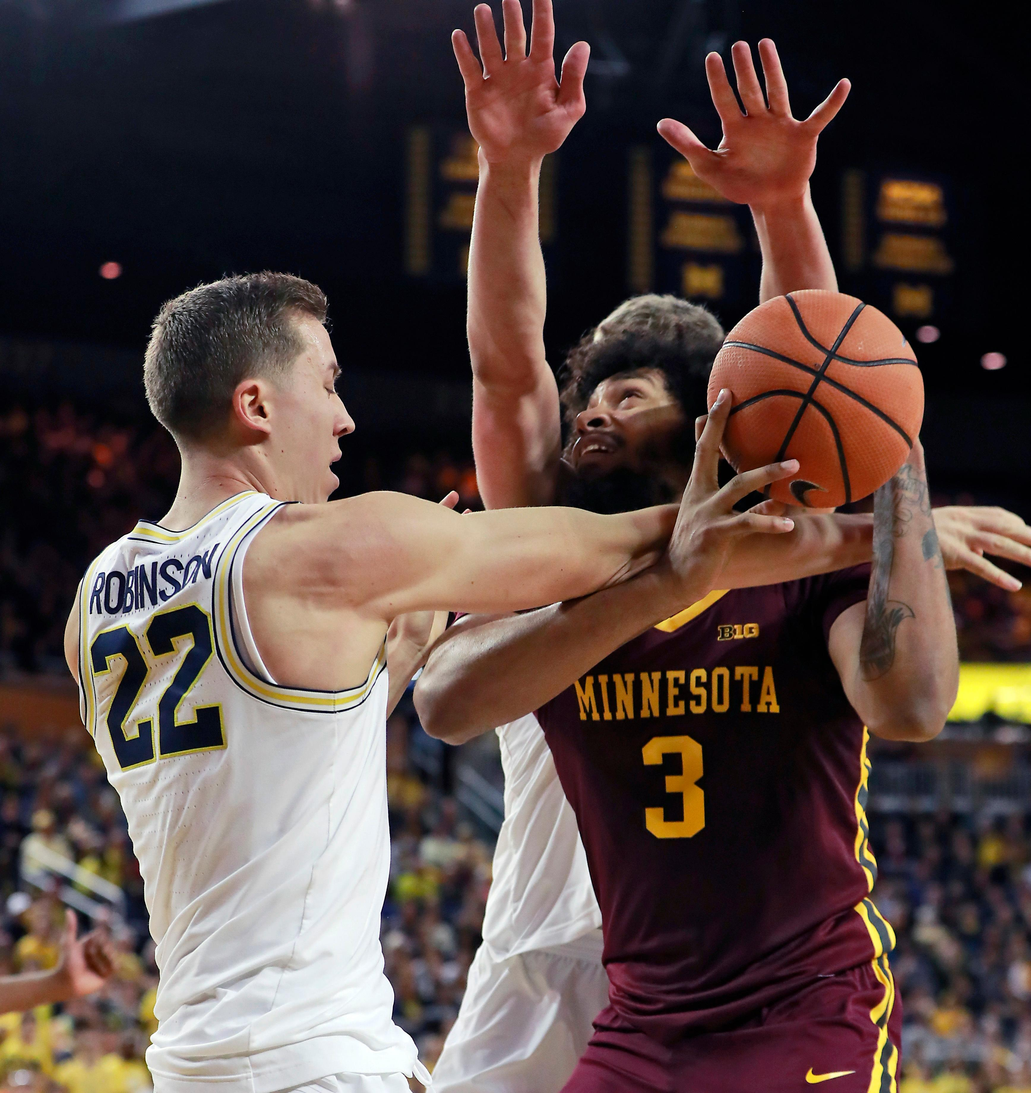 Michigan guard Duncan Robinson (22) reaches in and fouls Minnesota forward Jordan Murphy (3) during the first half of an NCAA college basketball game, Saturday, Feb. 3,2018, in Ann Arbor, Mich. (AP Photo/Carlos Osorio)