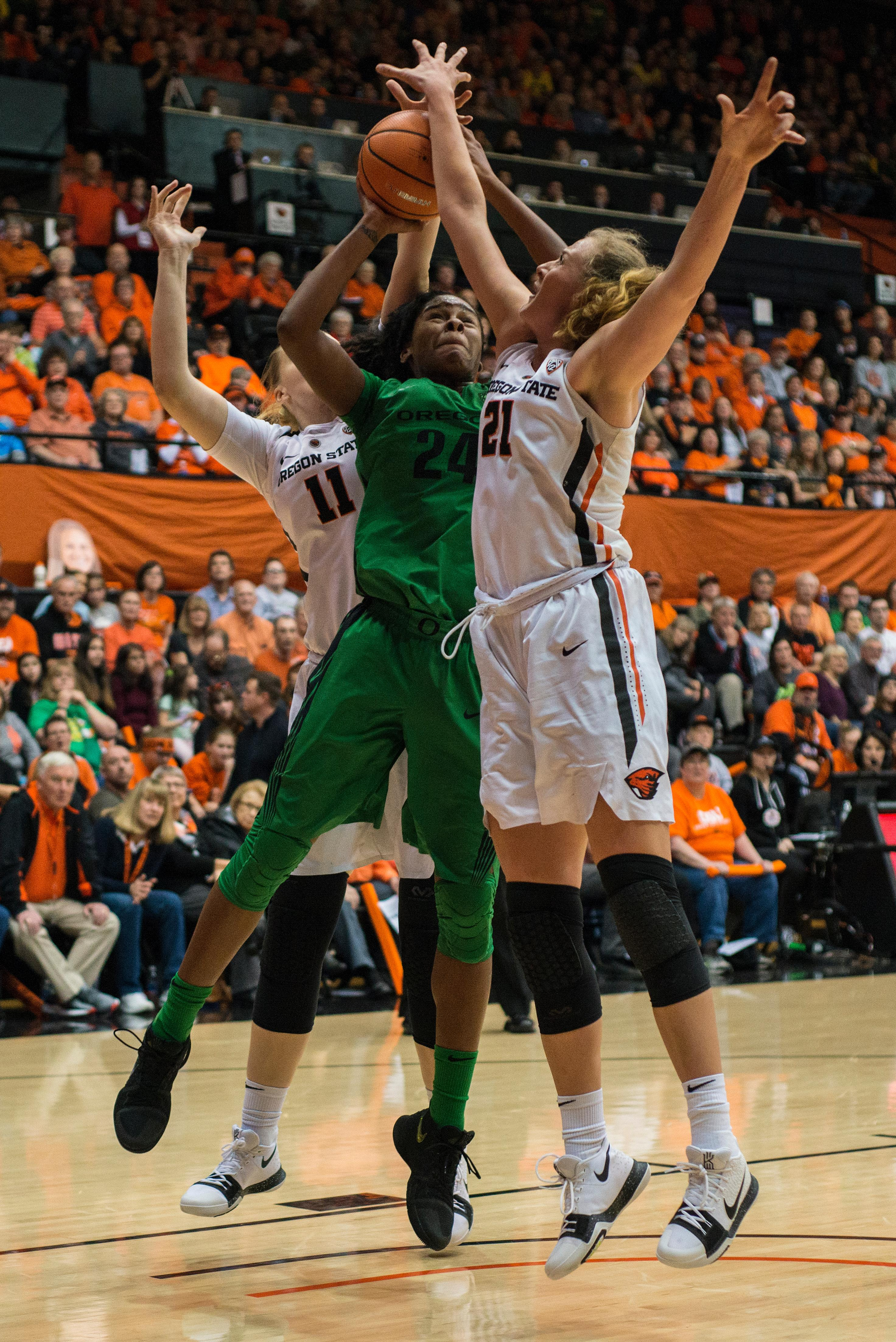 Oregon Ducks guard Ruthy Hebard (#24) goes for the shot as Oregon State Beavers centers Marie Gülich (#21) and Joanna Grymek (#11) surround her.The Oregon Ducks were defeated by the Oregon State Beavers 85-79 on Friday night in Corvallis. Sabrina Ionescu scored 35 points and Ruthy Hebard added 24. The Ducks will face the Beavers this Sunday at 5 p.m. at Matthew Knight Arena. Photo by Abigail Winn, Oregon News Lab