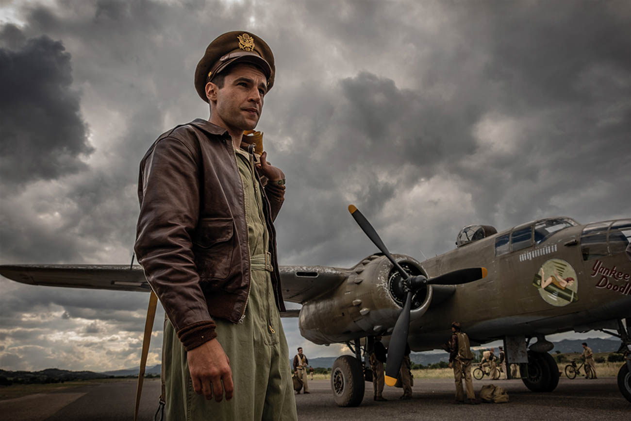 "Actor Christopher Abbott (pictured) stars as Captain John Yossarian in Catch-22—a miniseries produced by George Clooney on Hulu. He's standing in front of ""Yankee Doodle,"" a B-25 bomber plane owned and operated by the Tri-State Warbird Museum in Batavia. The museum flew the WWII aircraft to Italy to be featured in the show. / Image: Philippe Antonello via Catch-22 on Hulu // Published: 10.15.19<br>"