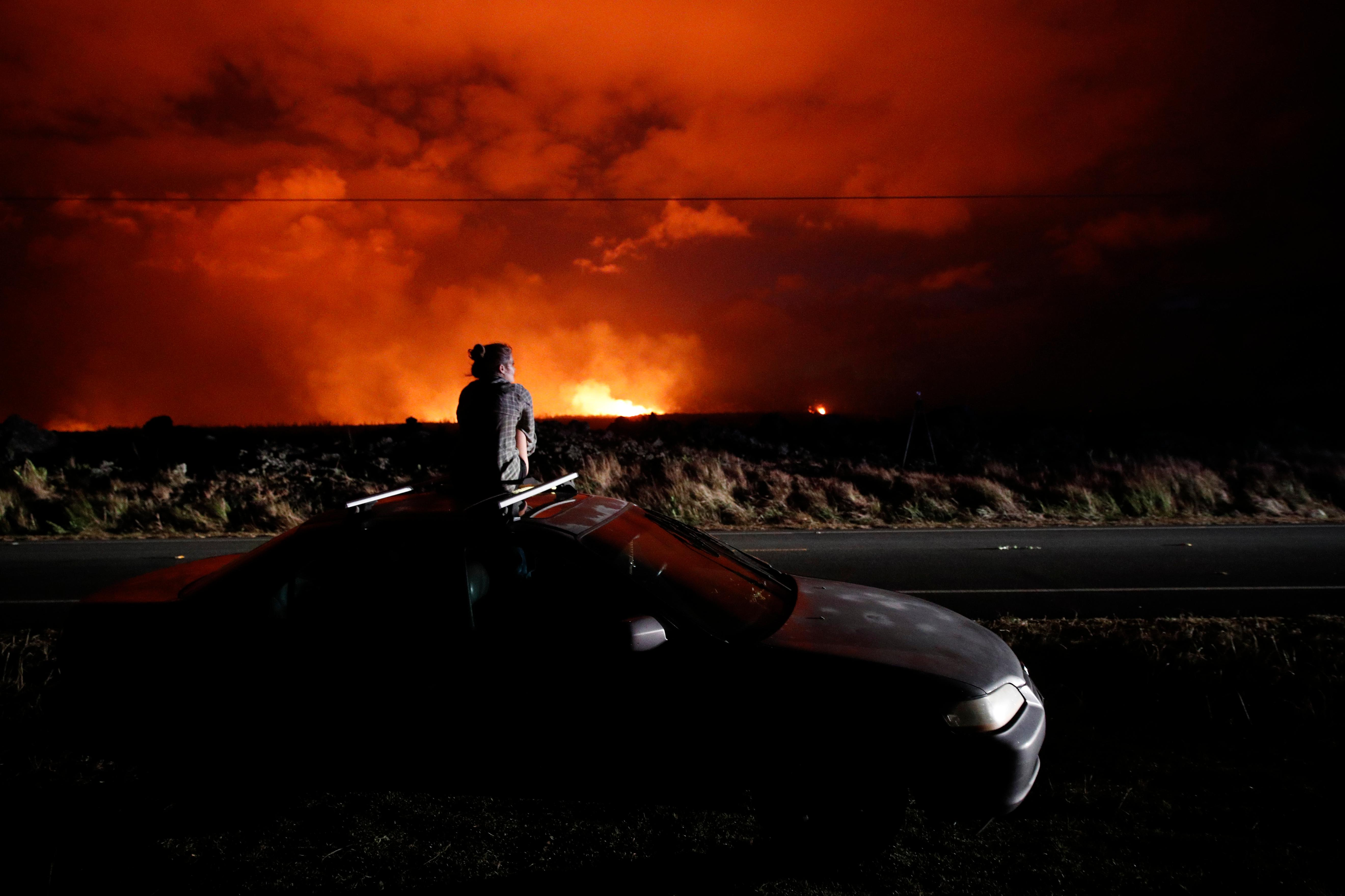 Brittany Kimball watches as lava erupts from a fissure near Pahoa, Hawaii, Saturday, May 19, 2018. Two fissures that opened up in a rural Hawaii community have merged to produce faster and more fluid lava. Scientists say the characteristics of lava oozing from fissures in the ground has changed significantly as new magma mixes with decades-old stored lava. (AP Photo/Jae C. Hong)