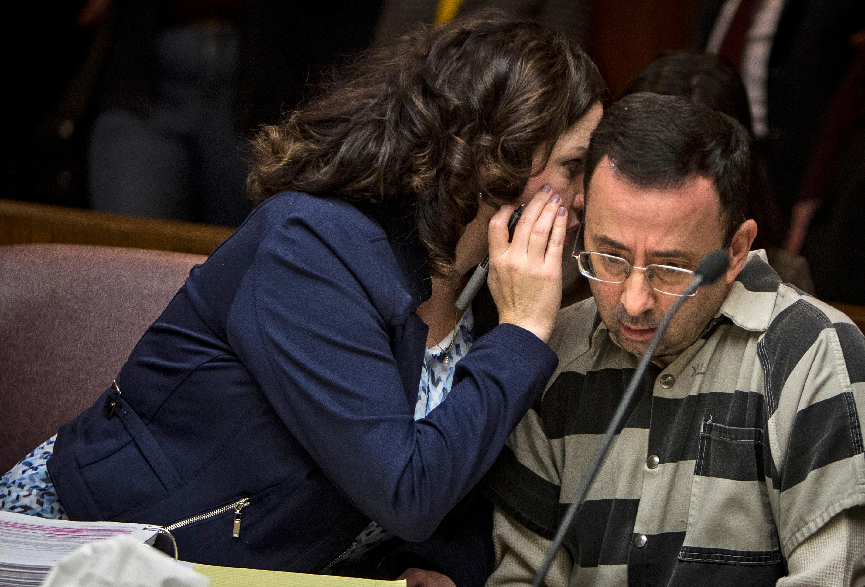 Shannon Smith, attorney for Dr. Larry Nassar whispers to her client during a preliminary hearing Friday, May 12, 2017, in Mason, Mich.. Nassar, a former Michigan State University doctor who also worked for USA Gymnastics, faces sexual assault charges charges. (Matthew Dae Smith/Lansing State Journal via AP)