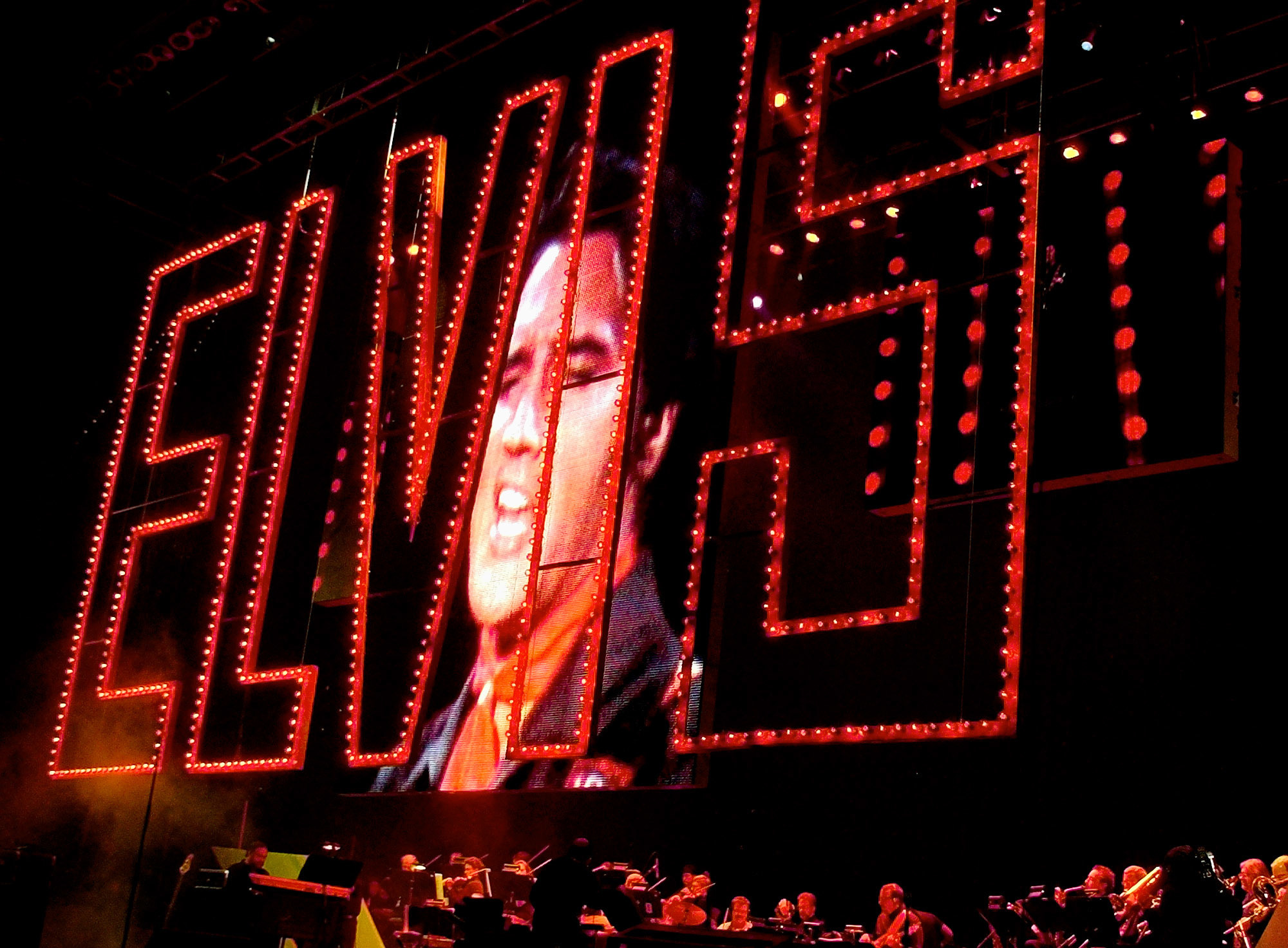 "This Aug. 16, 2002 file photo shows an image of Elvis Presley singing as his band plays below at the start of the Elvis Presley 25th Anniversary Concert in Memphis, Tenn. The red Elvis sign is from the 1968 Elvis 'comeback tour."" Friends and fans of late singer and actor Elvis Presley are descending on Memphis, Tennessee, for Elvis Week, the annual celebration of his life and career. It coincides with the 40th anniversary of the passing of Presley, who died on Aug. 16, 1977. (AP Photo/Stephan Savoia, File)"