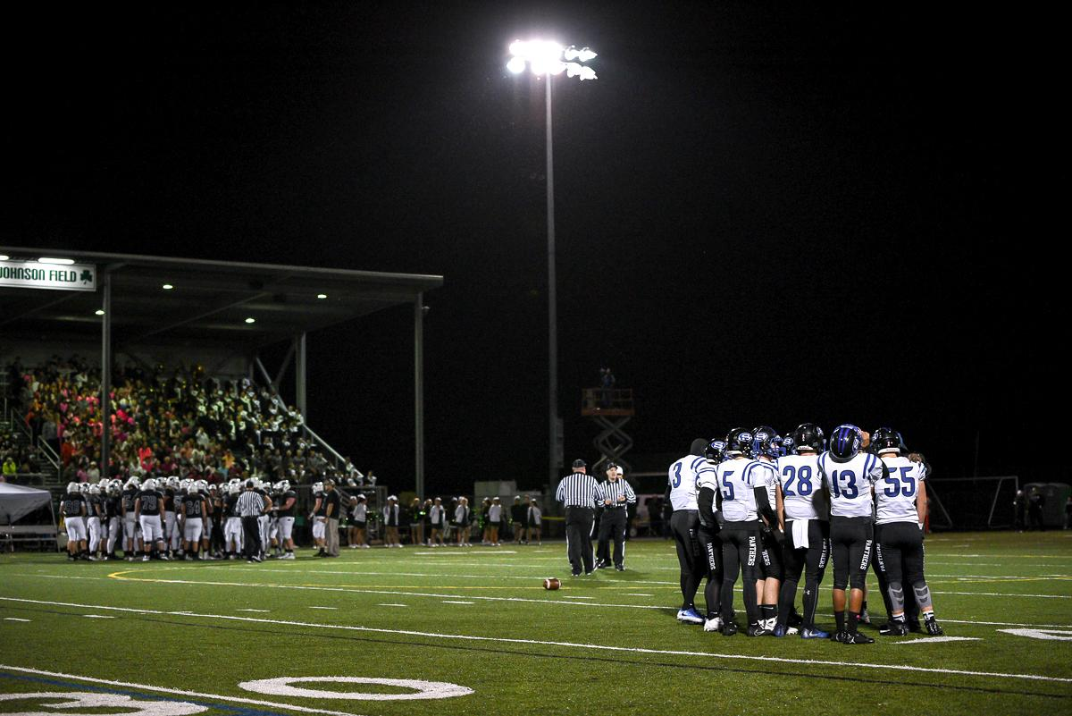 Both teams huddle up during South Medford's 31-14 victory over Sheldon. Photo by Jeff Dean, Oregon News Lab