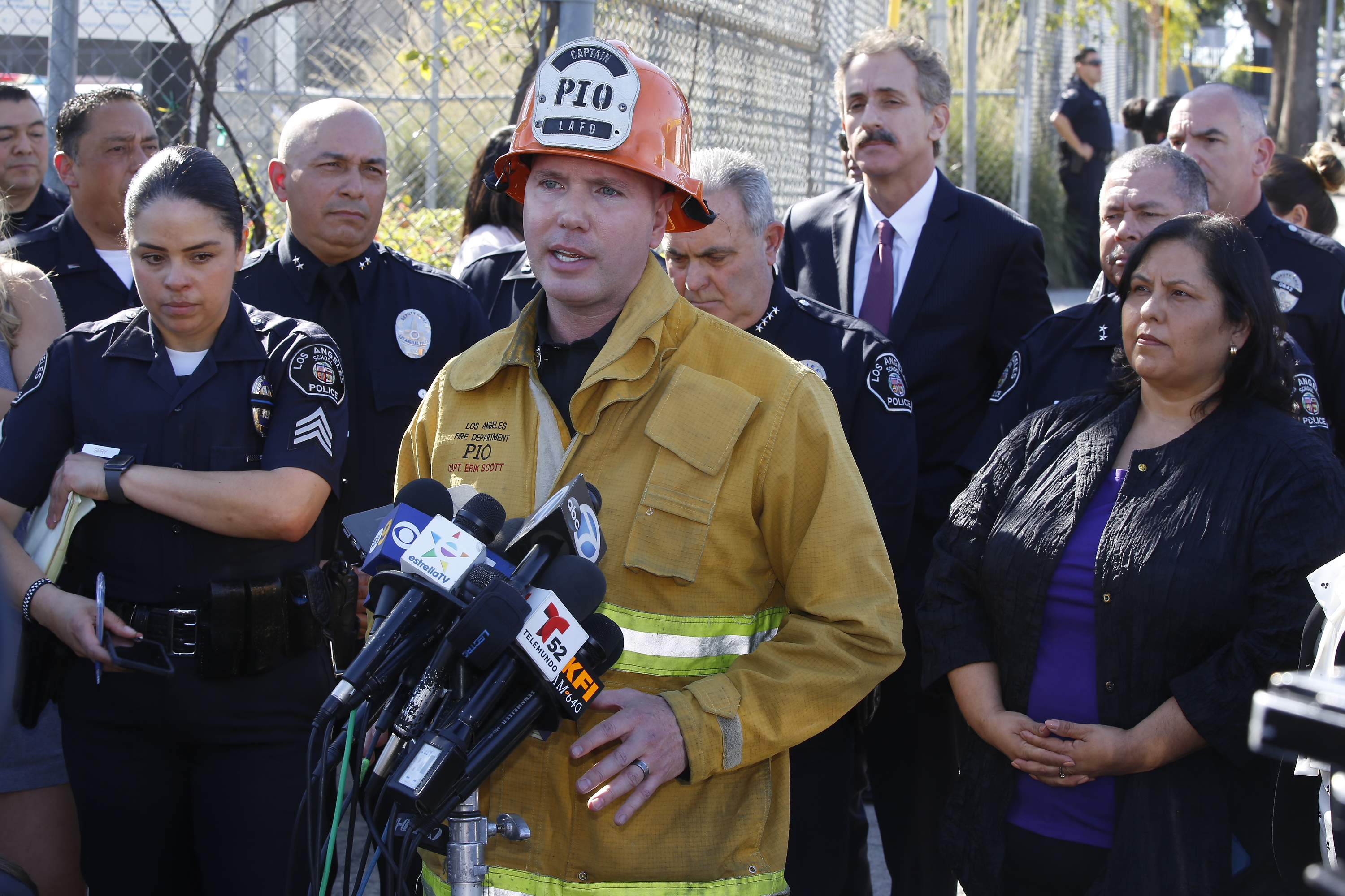 Los Angeles Fire department spokesman Erik Scott, center briefs the media outside the Belmont High School in Los Angeles Thursday, Feb. 1, 2018. Two students were shot and wounded, one critically, inside a Los Angeles middle school classroom Thursday morning and police arrested a female student believed to be 12 years old, authorities said. At right, Mónica García, Los Angeles Uinfied School District Board Member. (AP Photo/Damian Dovarganes)