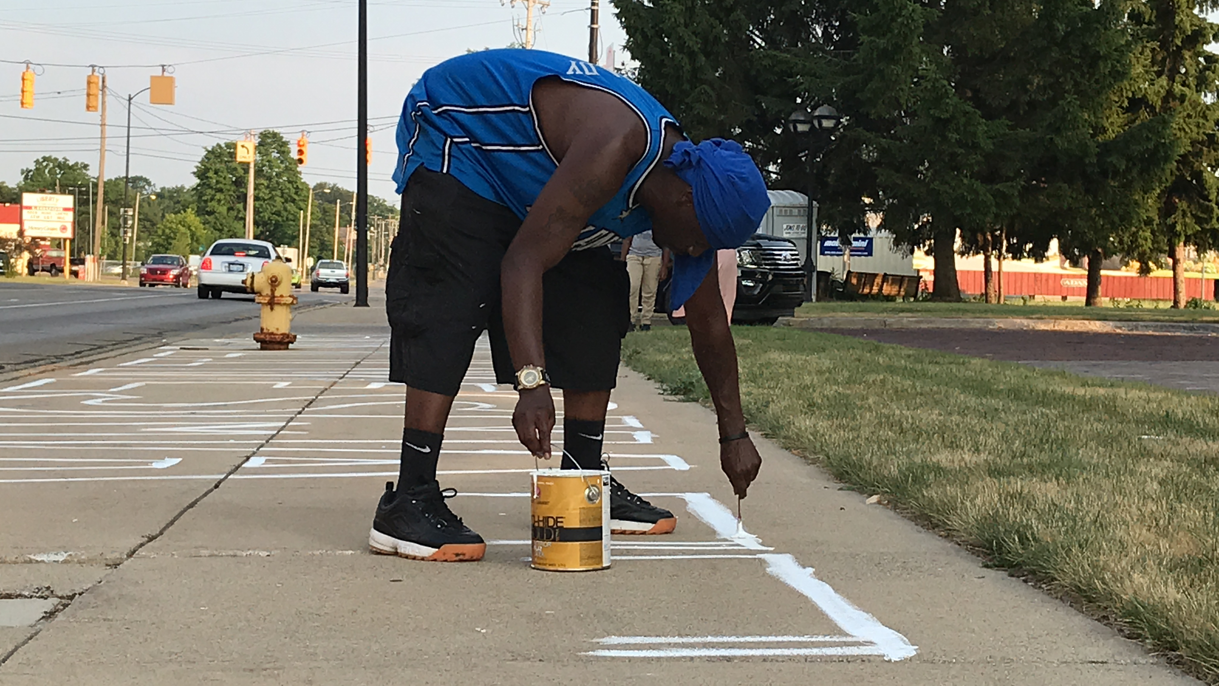 Gerald King of Battle Creek paints the T in Black Lives Matter on the sidewalk along East Michigan Avenue on Tuesday, July 7, 2020. The outlines are just the first step followed by the addition of Stand With Us to the east of the Back Lives Matter painting. (WWMT/Jason Heeres)