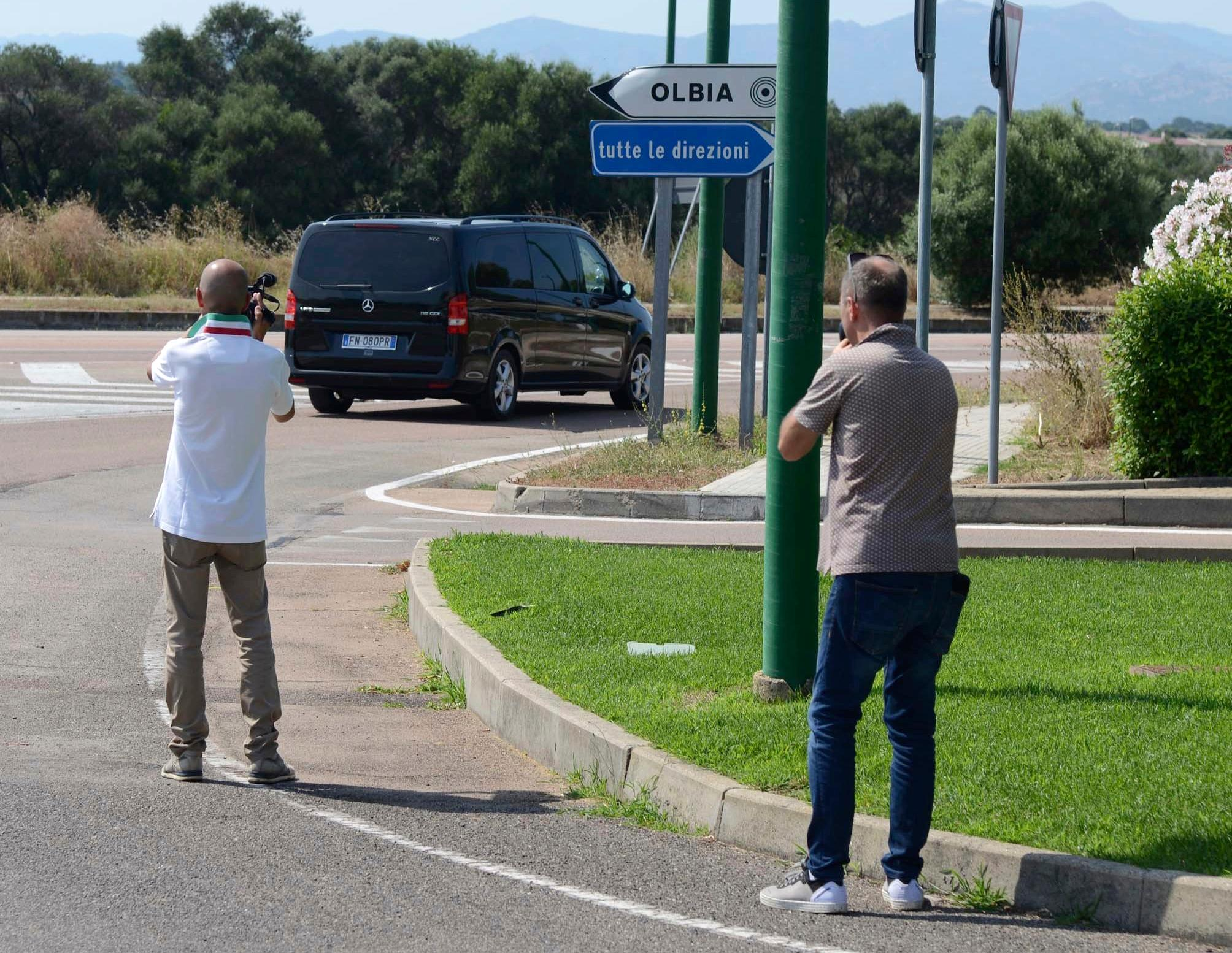 Reporters film a black van leaving the John Paul II hospital in the Sardinian town of Olbia, Italy, Tuesday, July 10, 2018. Actor George Clooney was taken to the hospital in Sardinia and released after being involved in an accident while riding his motorcycle, hospital officials said. (AP Photo/Antonio Satta)