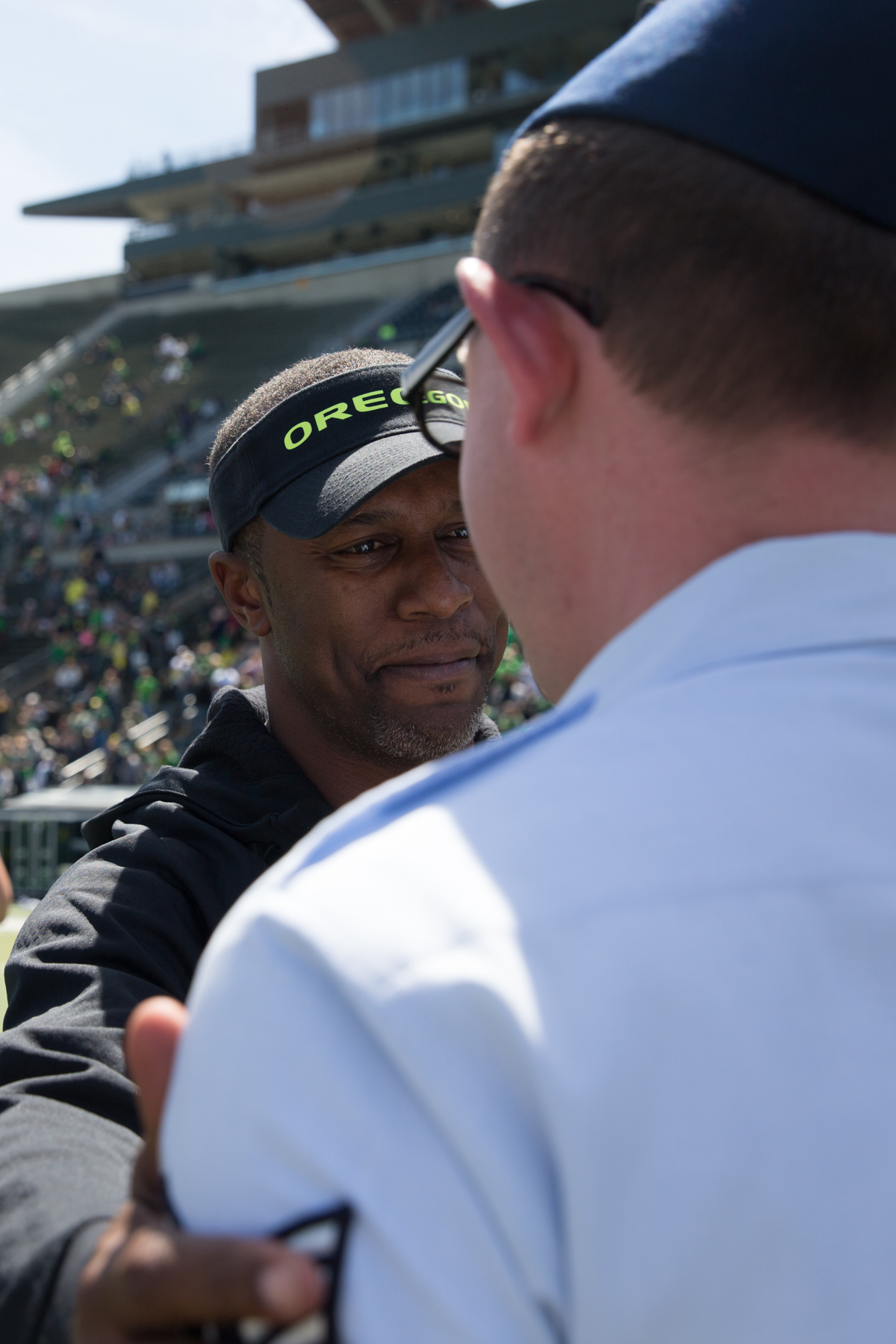 Oregon Ducks Head Coach Willie Taggart shakes hands with Air National Guard Technical Sergeant Andrew Saunders after presenting him with a game jersey. The 2017 Oregon Ducks Spring Game provided fans their first look at the team under new Head Coach Willie Taggart's direction.  Team Free defeated Team Brave 34-11 on a sunny day at Autzen Stadium in Eugene, Oregon.  Photo by Austin Hicks, Oregon News Lab