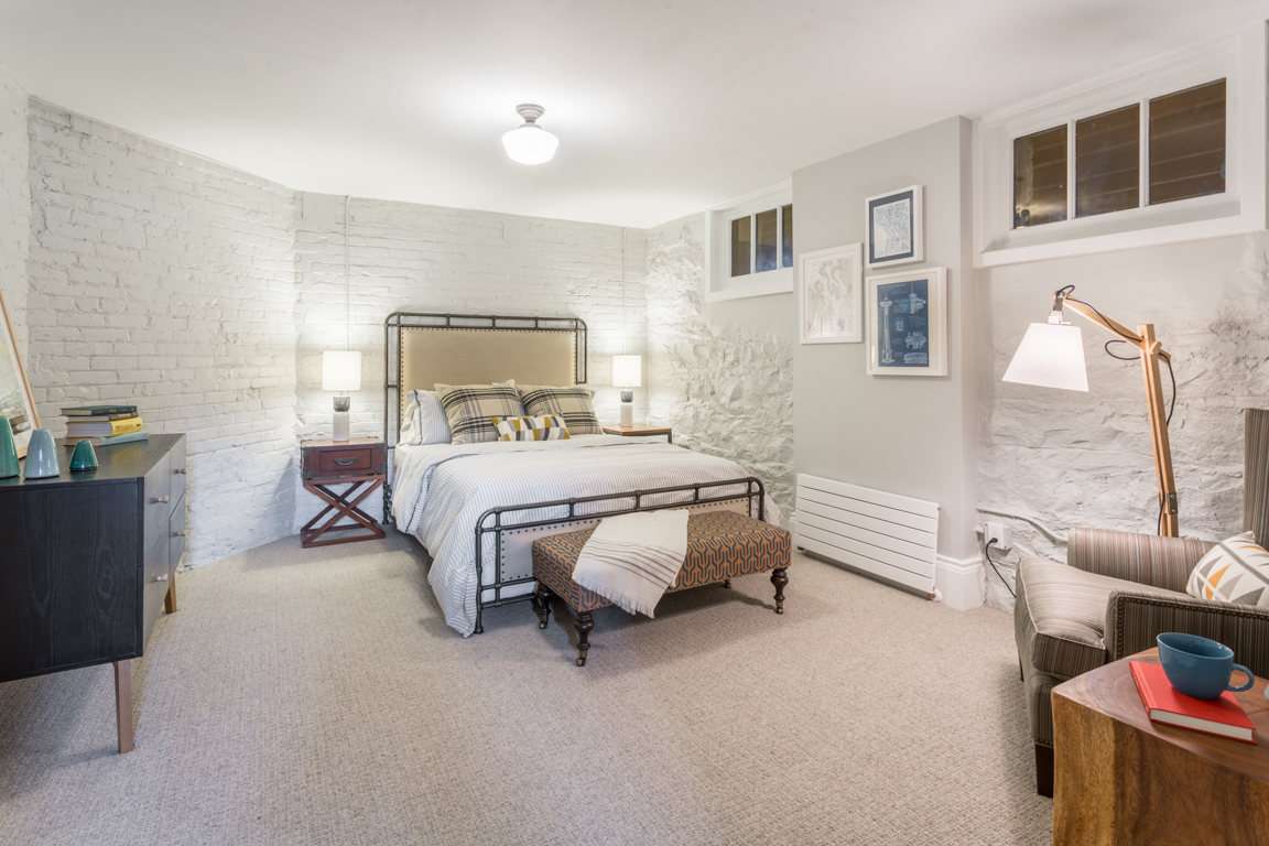 The finished basement guest room of the Ambrose features a walk-in closet and original exposed brick walls.