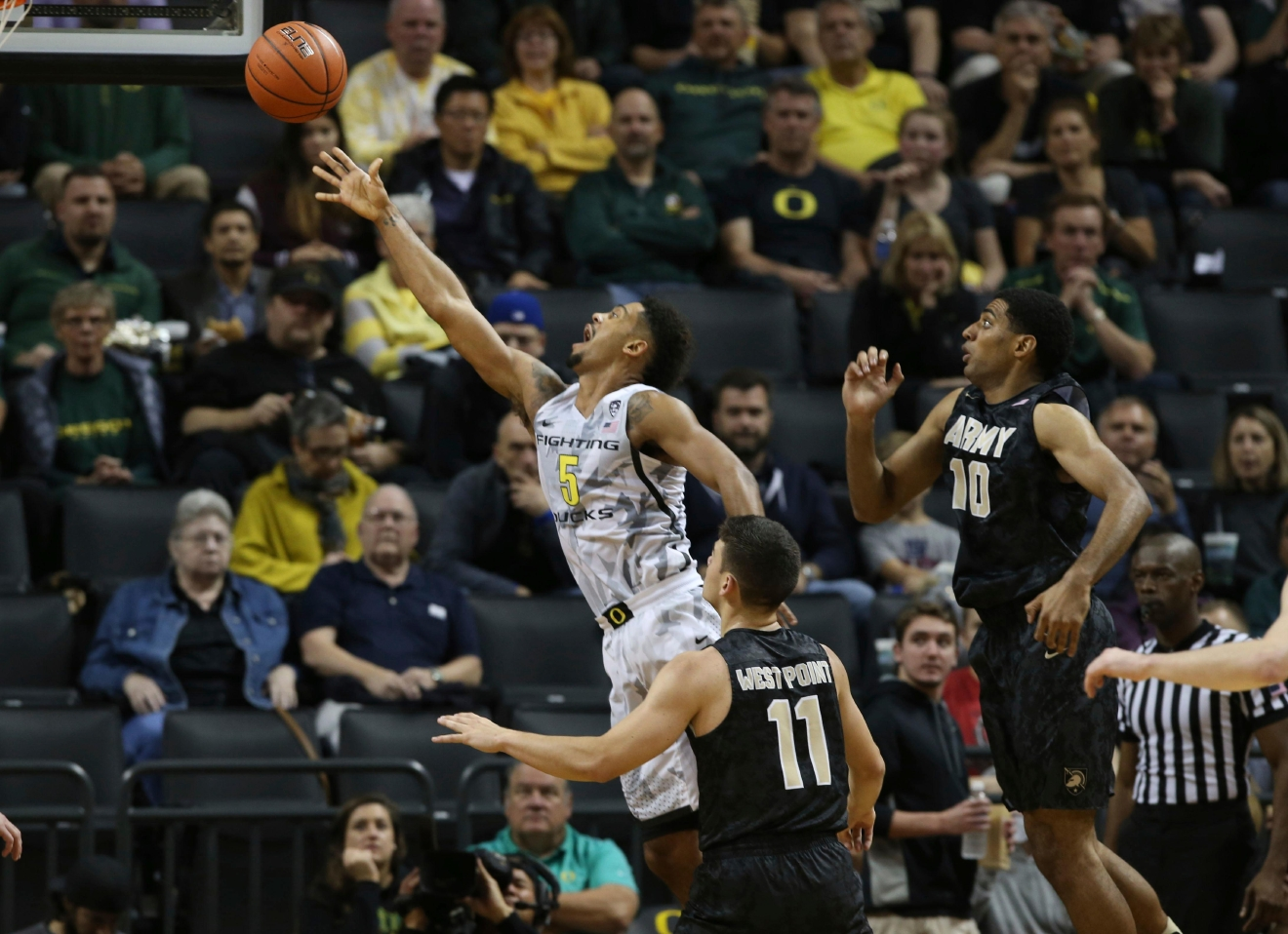 Oregon's Tyler Dorsey, left, releases a shot next to Army's Thomas Funk and Kennedy Edwards during the second half of an NCAA college basketball game Friday, Nov. 11, 2016, in Eugene, Ore. (AP Photo/Chris Pietsch)