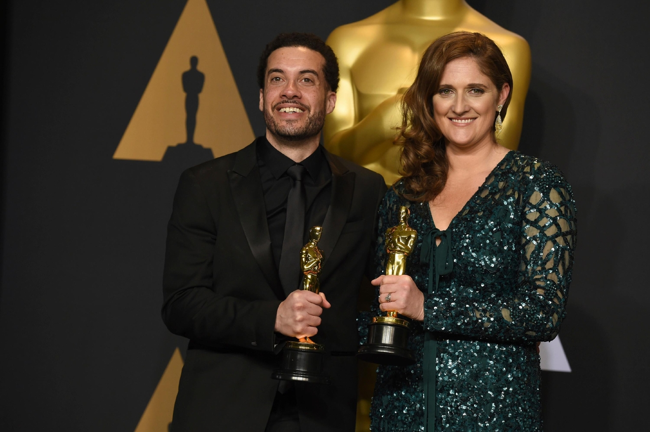 Ezra Edelman, left, and Caroline Waterlow pose in the press room at the Oscars on Sunday, Feb. 26, 2017, at the Dolby Theatre in Los Angeles. (Photo by Jordan Strauss/Invision/AP)