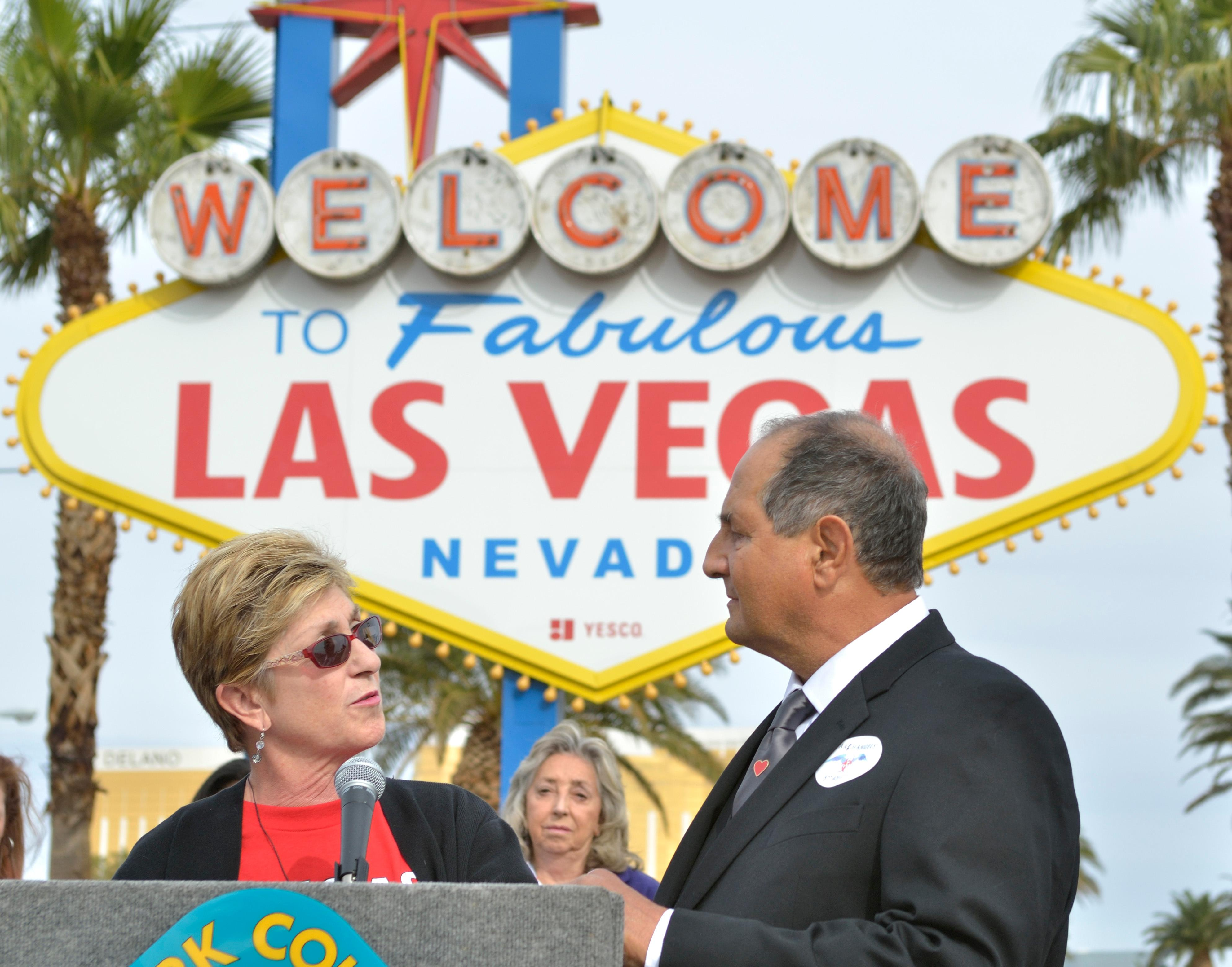 "Clark County Commissioner Chris Giunchigliani, left, speaks as Greg Zanis listens during ""Greg Zanis Day"" at the Welcome to Fabulous Las Vegas sign on the Las Vegas Strip on Sunday, Nov. 12, 2017. Zanis, a carpenter from Aurora, Ill., was recognized by the Clark County Commision for creating 58 crosses memorializing those who died during the Route 91 Harvest festival shooting on Oct. 1. The crosses were later moved to the Clark County Museum for its permanent collection. [Bill Hughes/Las Vegas News Bureau]"