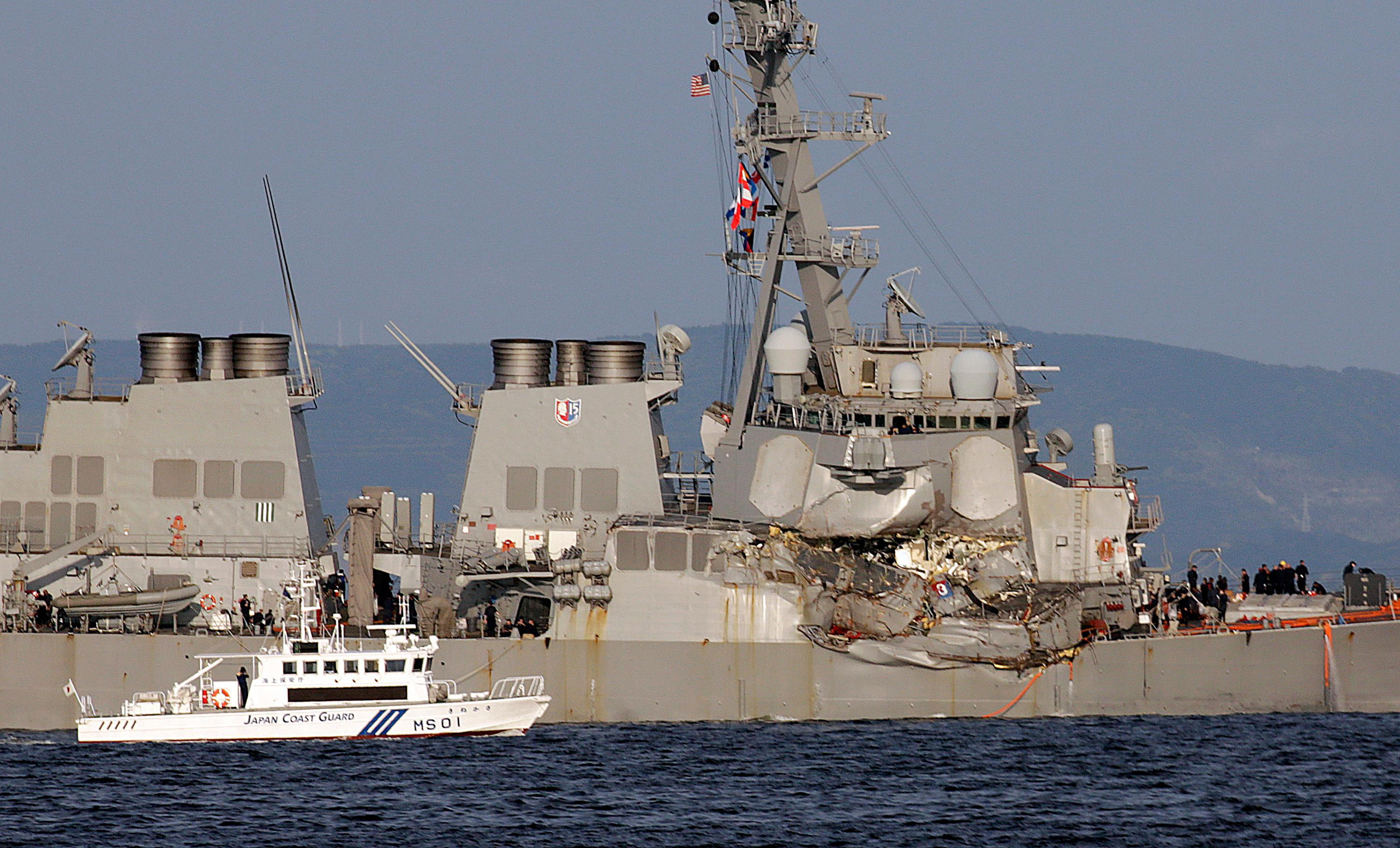 A Japan Coast Guard baot goes along with the damaged USS Fitzgerald near the U.S. Naval base in Yokosuka, southwest of Tokyo, after the U.S. destroyer collided with the Philippine-registered container ship ACX Crystal in the waters off the Izu Peninsula Saturday, June 17, 2017. Crew members from the destroyer USS Dewey were helping stabilize the damaged USS Fitzgerald after its collision off the coast of Japan before dawn Saturday, leaving seven sailors missing and at least three injured. (AP Photo/Eugene Hoshiko)
