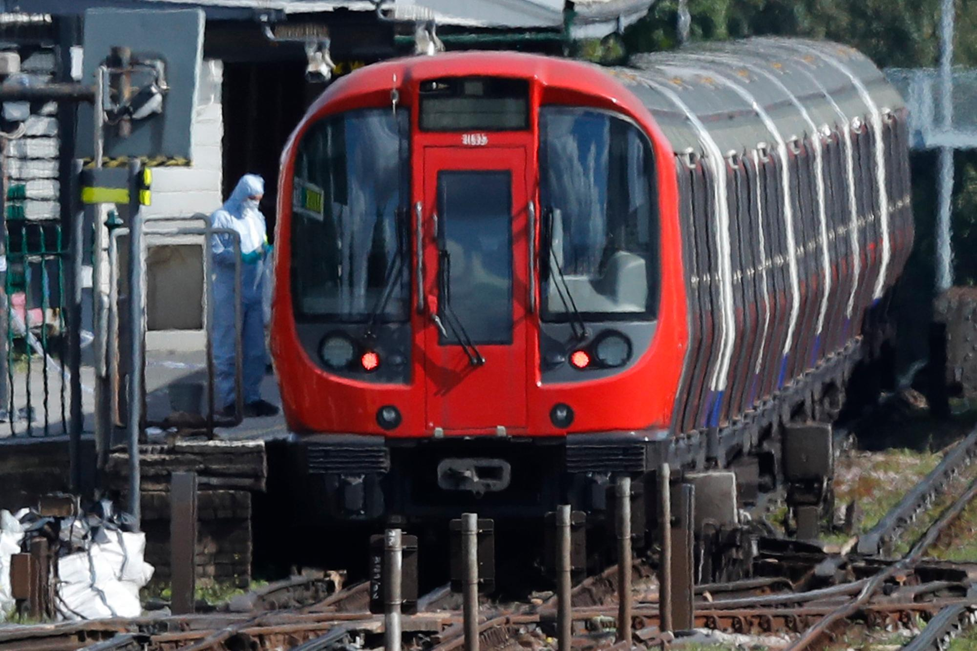 A police forensic officer stands beside the train where an incident happened, that police say they are investigating as a terrorist attack, at Parsons Green subway station in London, Friday, Sept. 15, 2017. A bucket wrapped in an insulated bag caught fire on a packed London subway train Friday, sending commuters stampeding in panic at the height of the morning rush hour. (AP Photo/Frank Augstein)