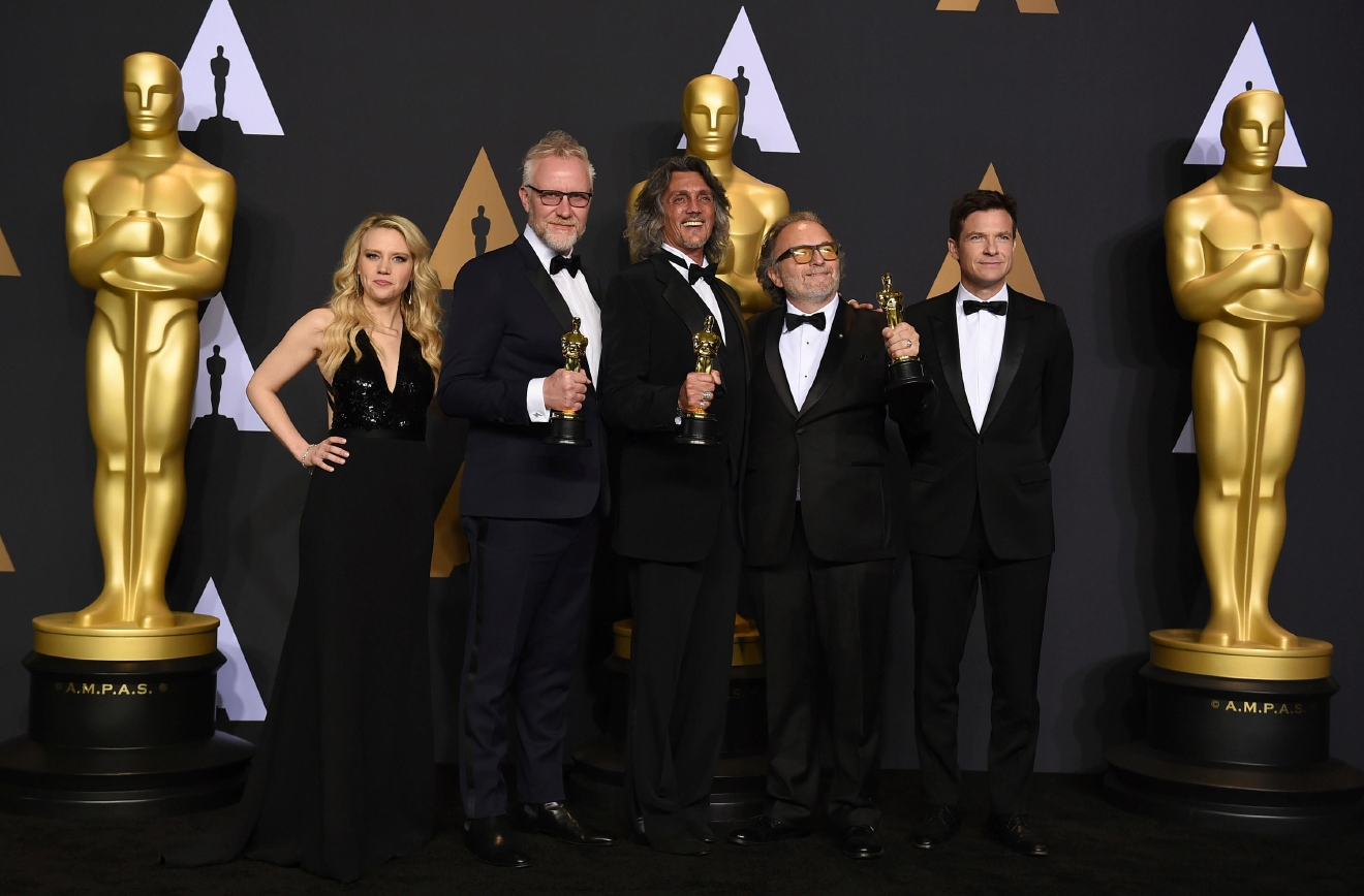 "Christopher Nelson, second from left, Giorgio Giorgio, center, and Alessandro Bertolazzi, second from right, winners of the award for best makeup and hairstyling for ""Suicide Squad"" pose in the press room with Kate McKinnon, left, and Jason Bateman, right, at the Oscars on Sunday, Feb. 26, 2017, at the Dolby Theatre in Los Angeles. (Photo by Jordan Strauss/Invision/AP)"