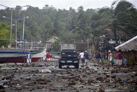Debris litter the road by the coastal village in Legazpi city following a storm surge brought about by powerful Typhoon Haiyan in Albay province Friday, Nov. 8, 2013.