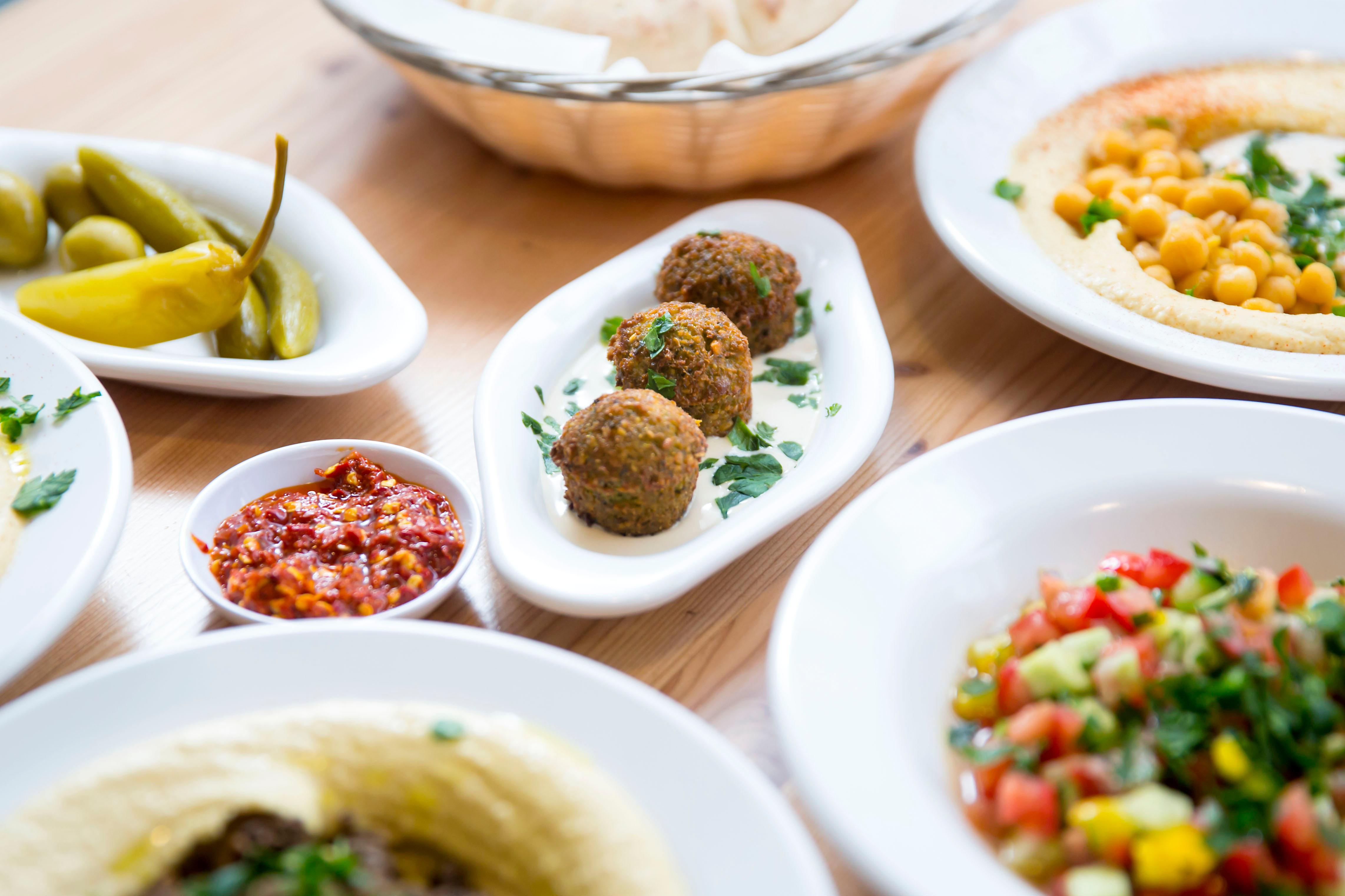 "A half order of falafel sits in the middle of a typical Israeli hummus bar meal.<p></p><p>Aviv Hummus Bar is a 100% Israeli hummus bar, straight from the streets of Tel Aviv. And now, it's on Capitol Hill! Fun fact: Hummus literally means chickpeas. And while the west has kind of appropriated hummus and made it its own thing, traditional hummus isn't a sauce, or a dip, it's supposed to be a eaten as a meal consisting of smashed chickpeas, ""tahina"" and lemon. Enter Aviv Hummus Bar - trying to educate through this food. The Hummus Bar is located on 107 15th Ave E, Seattle. (Image: Sy Bean / Seattle Refined){&nbsp;}<br></p>"