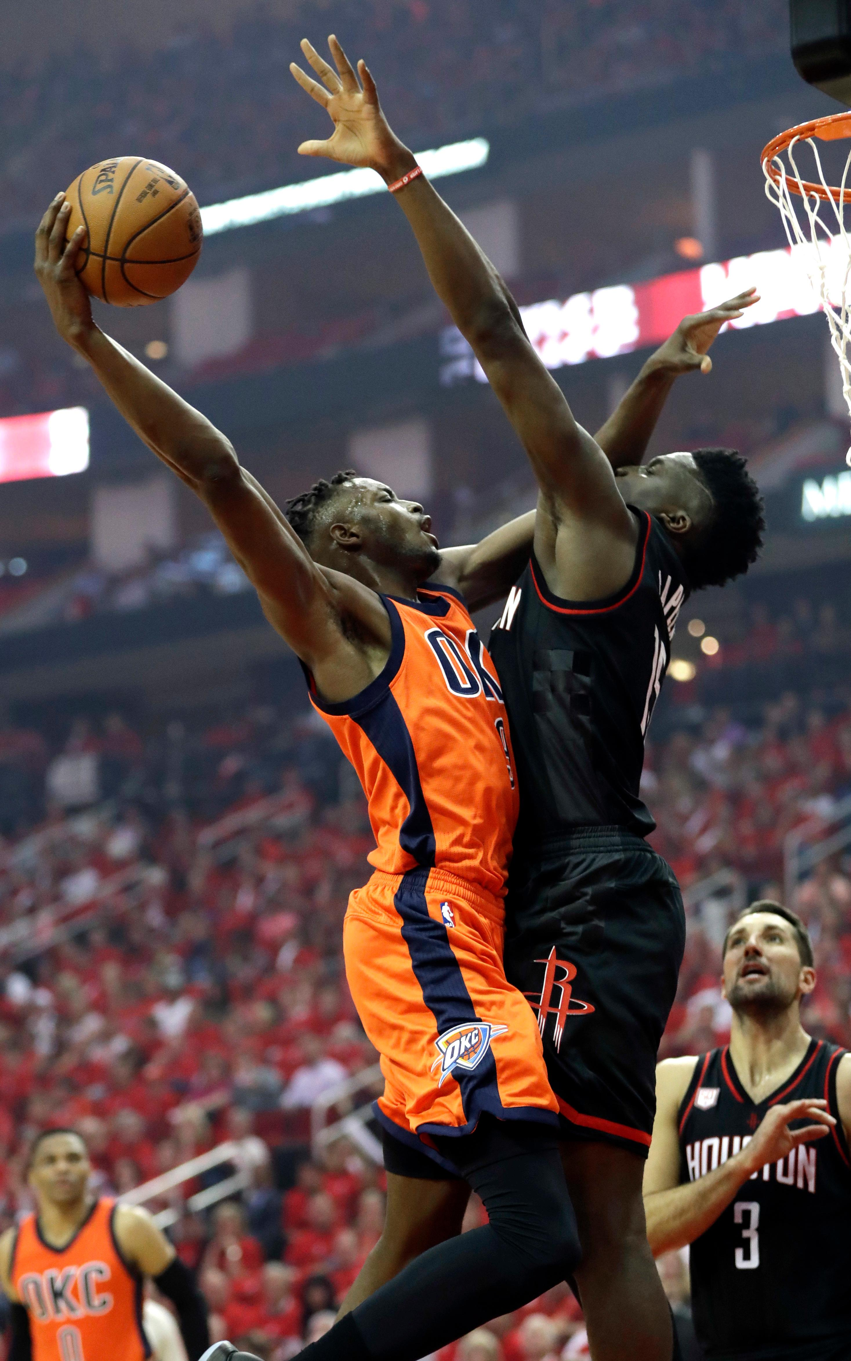 Oklahoma City Thunder's Jerami Grant, left, goes up for a shot as Houston Rockets' Clint Capela defends during the first half in Game 1 of an NBA basketball first-round playoff series, Sunday, April 16, 2017, in Houston. (AP Photo/David J. Phillip)