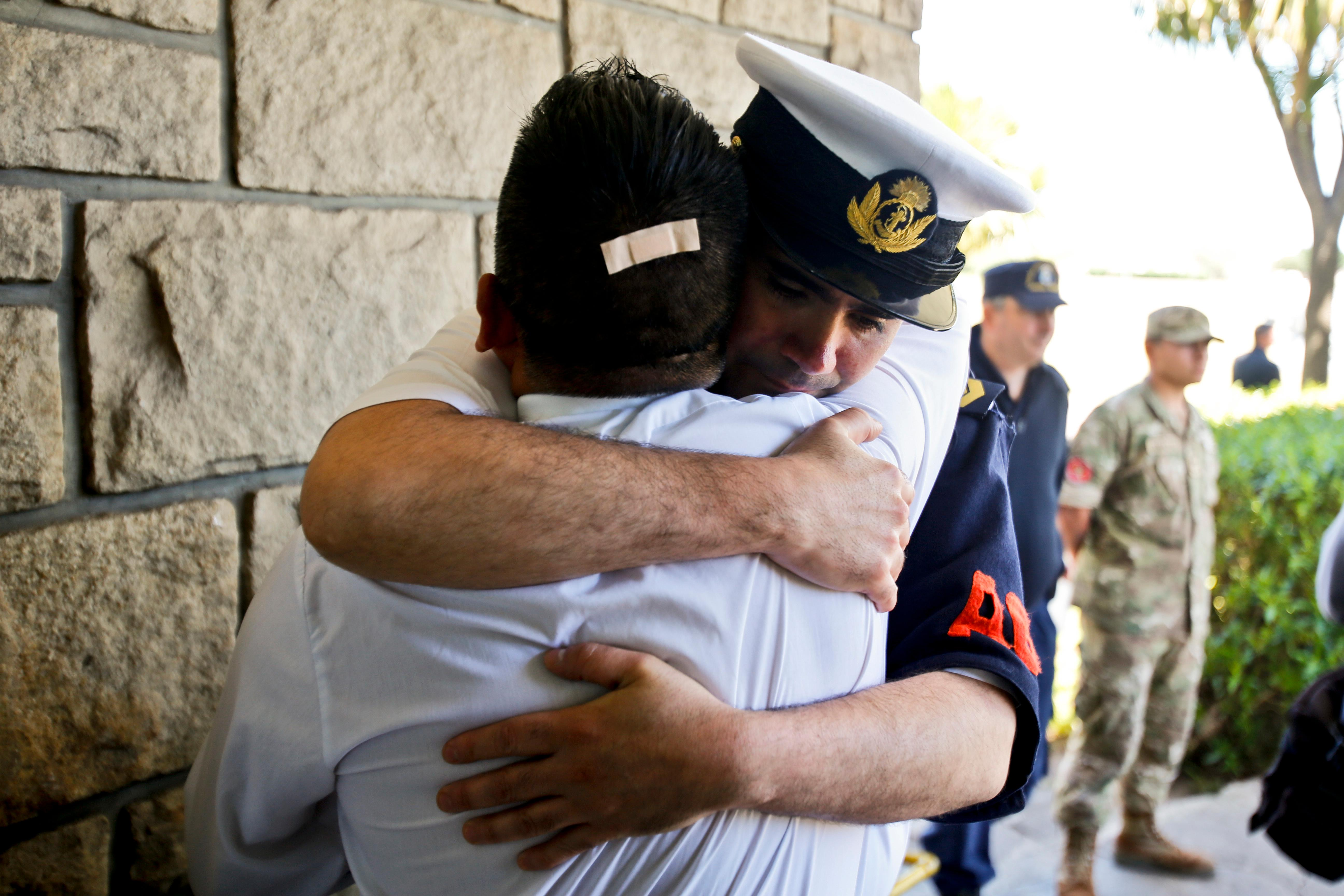 Argentine Navy officials embrace inside the Mar de Plata Naval Base after Argentina's Navy announced that a sound detected during the search for the missing ARA San Juan submarine is consistent with that of an explosion, in Mar de Plata, Argentina, Thursday, Nov. 23, 2017. A Navy spokesman said that the relatives of the crew have been informed and that the search will continue until there is full certainty about the fate of the ARA San Juan. He said there was no sign the explosion might be linked to any attack on the sub. (AP Photo/Esteban Felix)