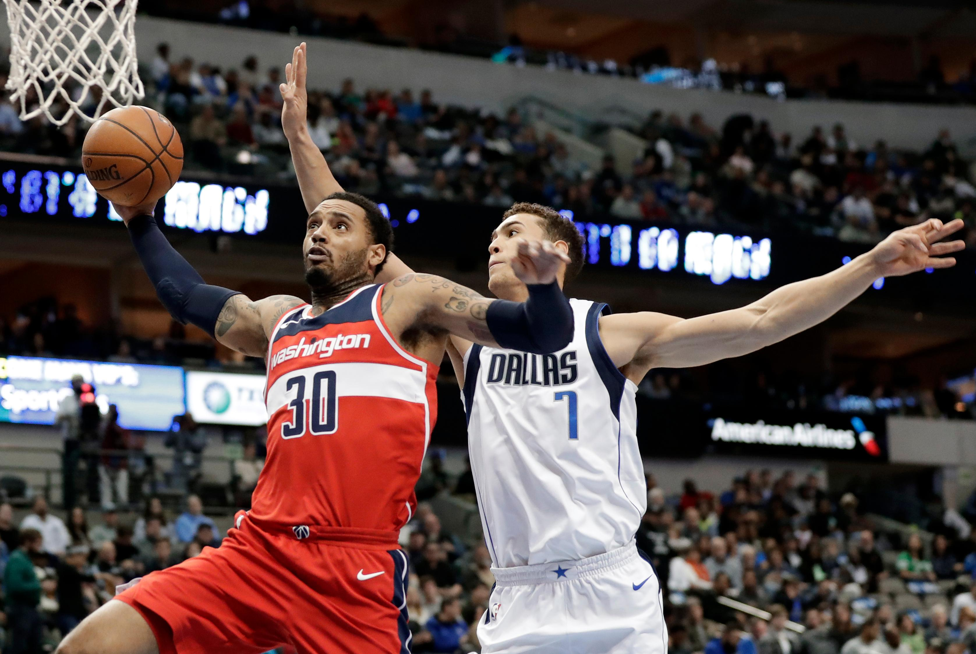 Washington Wizards forward Mike Scott (30) goes up for a shot as Dallas Mavericks' Dwight Powell (7) defends in the second half of an NBA basketball game, Monday, Jan. 22, 2018, in Dallas. (AP Photo/Tony Gutierrez)