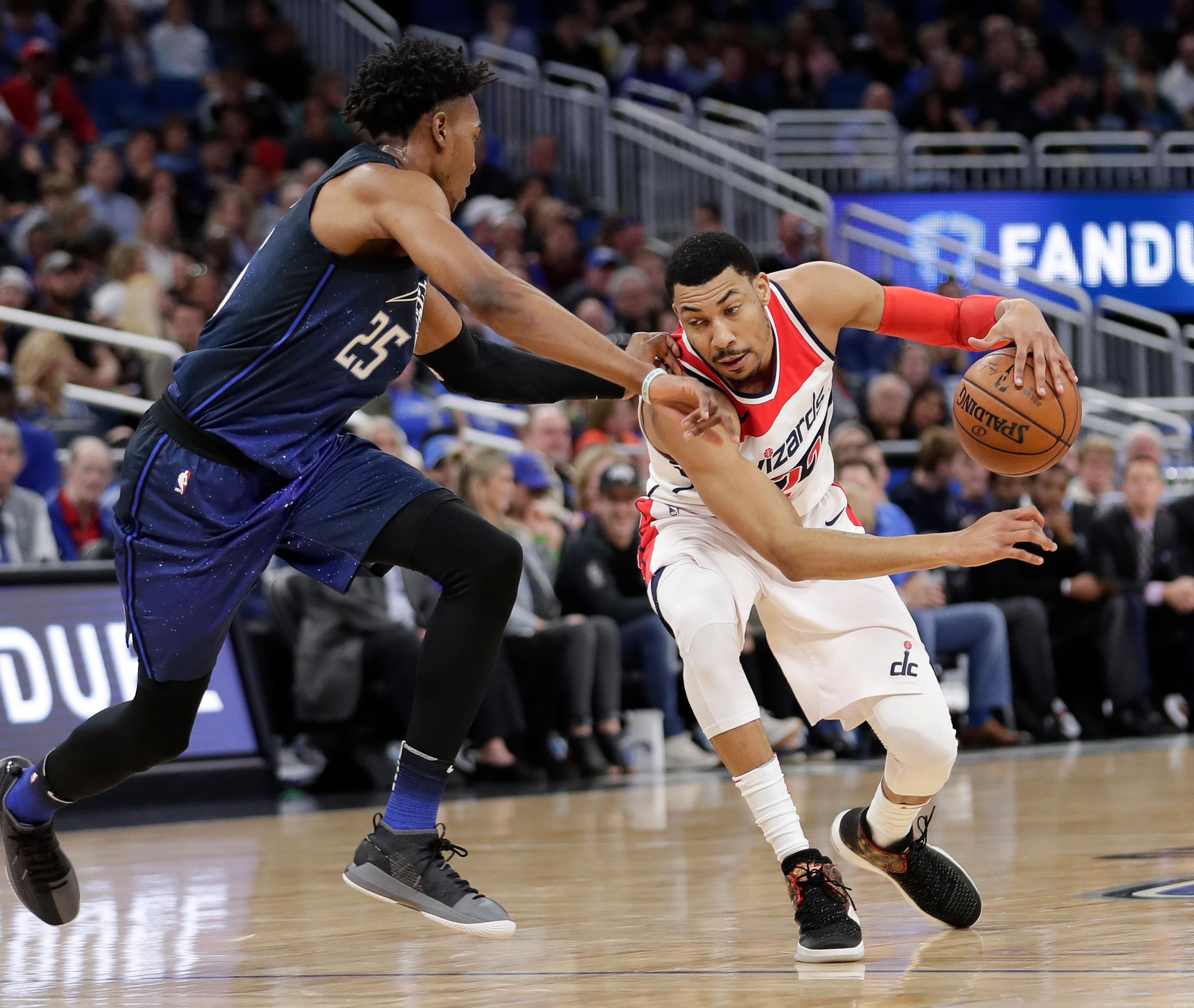 Washington Wizards' Otto Porter Jr., right, drives past Orlando Magic's Wesley Iwundu (25) during the first half of an NBA basketball game Saturday, Feb. 3, 2018, in Orlando, Fla. (AP Photo/John Raoux)