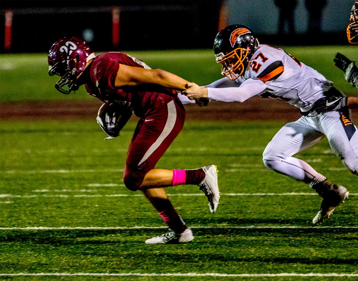 Willamette's Tanner Webb (#20) attempts to evade Roseburgs' Colin Rietmann (#27). The Roseburg Indians defeated the Willamette Wolverines 21-20 at Willamette on Friday. Photo by August Frank, Oregon News Lab