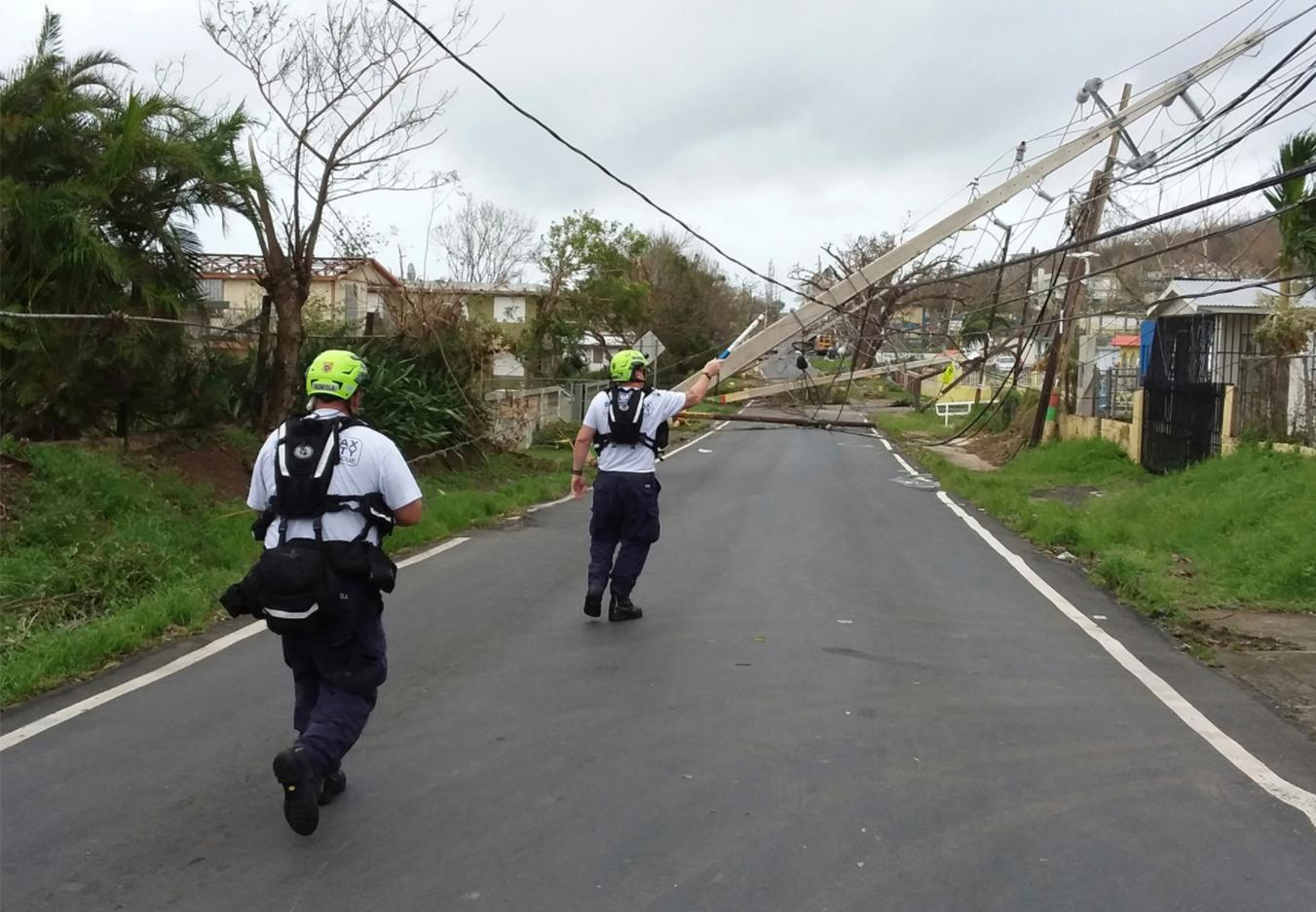 In this Friday, Sept. 22, 2017 photo provided by the Virginia Task Force 1, crew members ultilize a hot stick to assess electrical lines in the aftermath of Hurricane Maria, in eastern Puerto Rico. Days after Maria ravaged Puerto Rico, flooding towns, crushing homes, millions on the island face the dispiriting prospect of weeks and perhaps months without electricity. (Virginia Task Force 1 via AP)