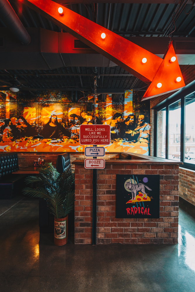 "The dining room is filled with eclectic paraphernalia, neon signs, and funky art. Mikey, the owner, describes the aesthetic as ""rock 'n roll pizza church."" / Image: Catherine Viox // Published: 4.4.19"