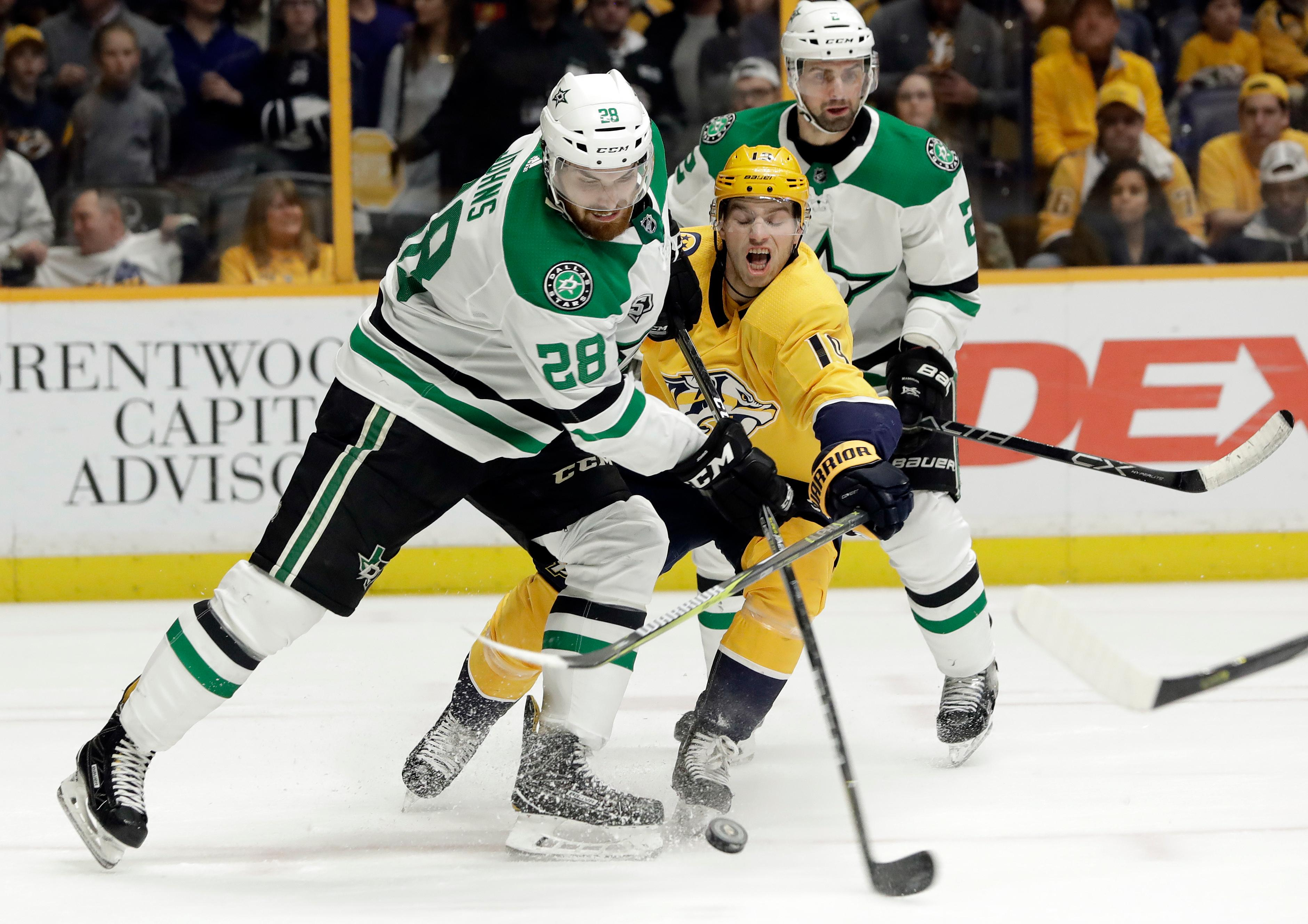 Dallas Stars defenseman Stephen Johns (28) and Nashville Predators center Calle Jarnkrok (19), of Sweden, battle for the puck in the second period of an NHL hockey game Tuesday, March 6, 2018, in Nashville, Tenn. (AP Photo/Mark Humphrey)