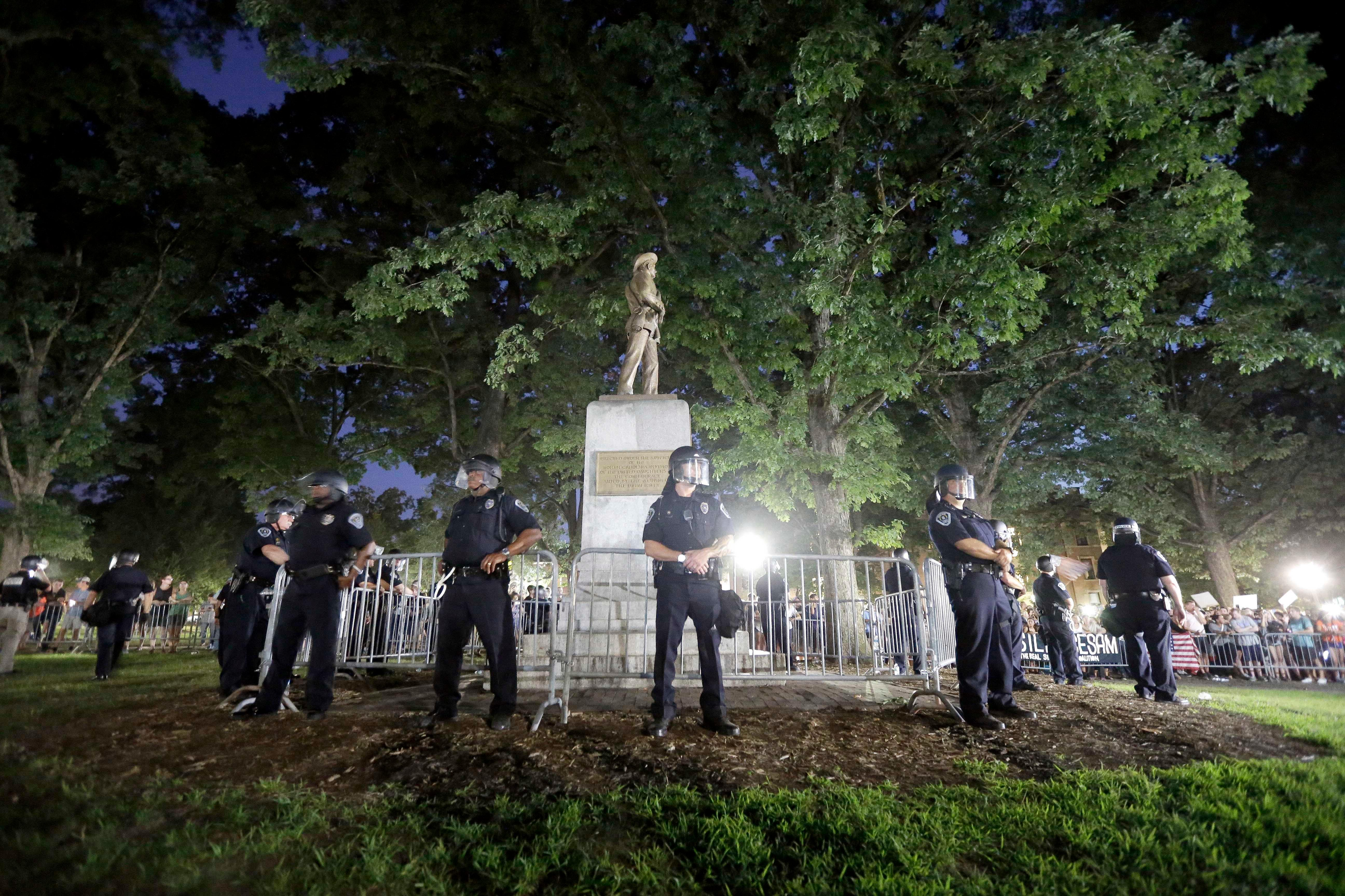 FILE - Police surround a Confederate monument during a protest to remove the statue at the University of North Carolina in Chapel Hill, N.C., Tuesday, Aug. 22, 2017. (AP Photo/Gerry Broome)