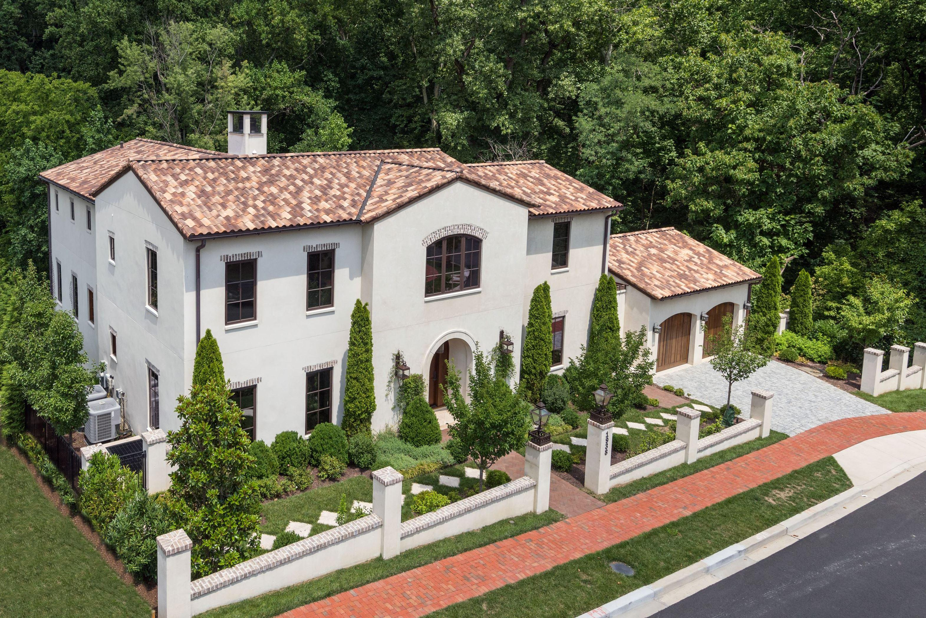 "You'd never guess that this Italian-inspired villa exists within the city limits, but it surely does! Built in 2016 by GTM Architects and Sandy Spring Builders, the 5-bedroom/6-bath estate looks like something straight out of ""Under the Tuscan Sun."" The home's amenities include beamed ceilings, multiple fireplaces, limestone counters, exotic imported European tiles, a wine cellar, a deluxe garden/potting room on the lower level and several multi-tiered terraces, patios and balconies all overlooking a private park and dramatic water fountain. (Image: Courtesy Homevisit)"