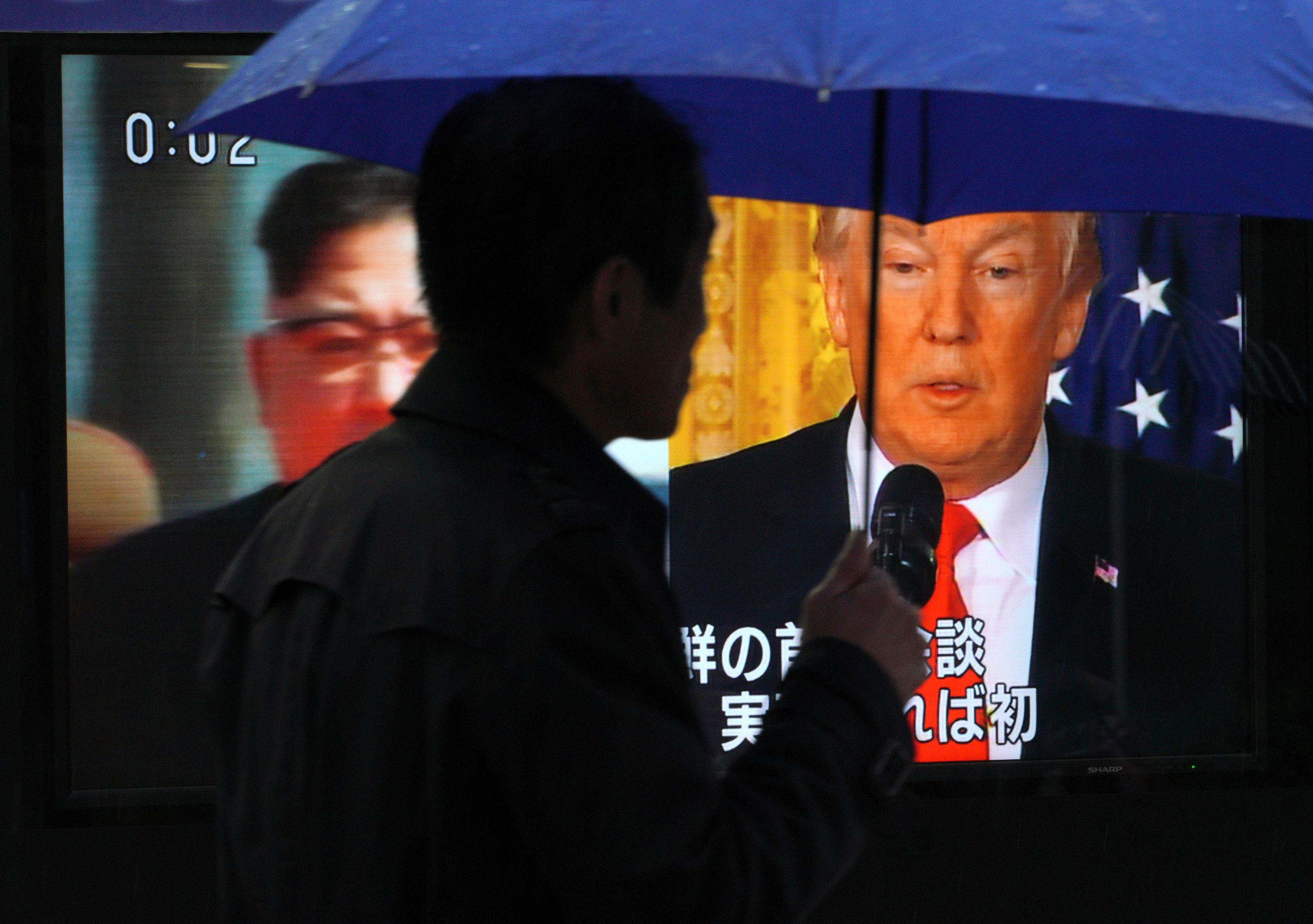 "A man watches a TV screen showing North Korean leader Kim Jong Un, left, and U.S. President Donald Trump, right, in Tokyo Friday, March 9, 2018. Trump has accepted an offer of a summit from the North Korean leader and will meet with Kim Jong Un by May, a top South Korean official said Thursday, in a remarkable turnaround in relations between two historic adversaries. The signs read: "" Trump has accepted an offer of a summit from the North Korean leader and will meet with Kim by May."" (AP Photo/Eugene Hoshiko)"