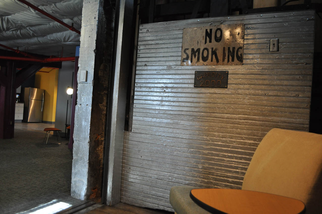 "Owners Alex Taylor and Tim Haines converted the old elevator shaft into a ""huddle room."" The elevator has been lifted and pinned in place. Old signage adds an additional old-school touch. / Image: Liz Engel // Published: 9.17.19"