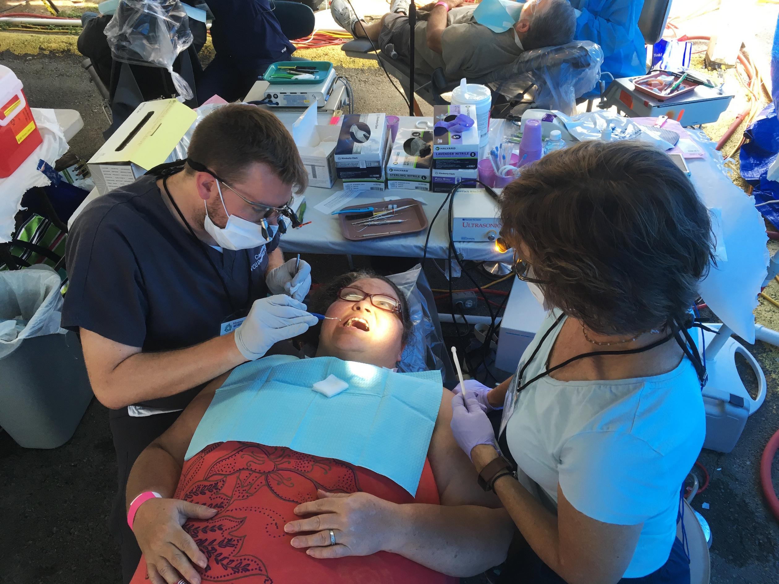 In this Friday, July 21, 2017 photo, dental student Carl Leiner, left, checks Lisa Kantsos teeth at the Remote Area Medical clinic in Wise, Va. Kantsos and hundreds of other uninsured patients came to the rural clinic for free dental and medical care. (AP Photo/Dylan Lovan)