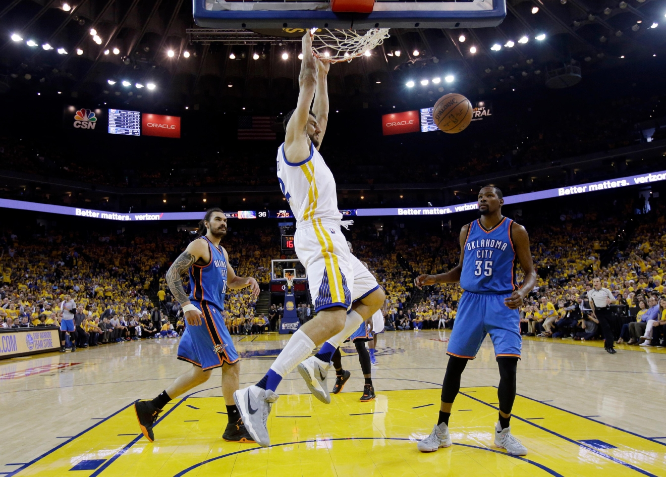 Golden State Warriors' Andrew Bogut, center, dunks past Oklahoma City Thunder's Kevin Durant (35) and Steven Adams, left, during the first half in Game 5 of the NBA basketball Western Conference finals Thursday, May 26, 2016, in Oakland, Calif. (AP Photo/Marcio Jose Sanchez)