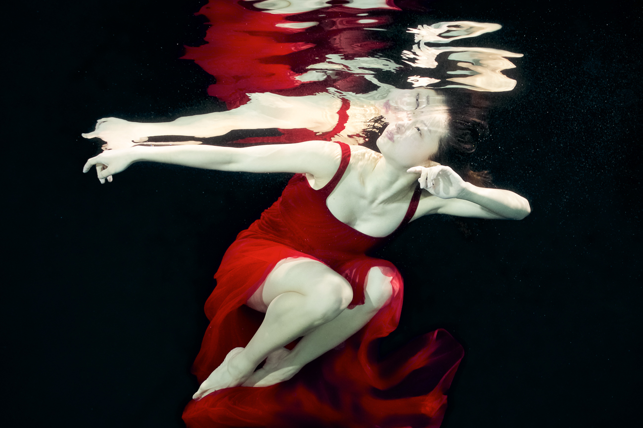 "Statement from artist Tina Gutierrez: ""In this underwater series, a watery environment invites the dancers to yield to the embrace of liquid instead of the greater forces of gravity that they normally experience. The added difficulty of working in the water creates a world of unexpected challenges for the dancer and the photographer. These images are only viewable from below the water and are so fleeting that they can only be captured by the speed of the camera. Due to its calmness yet danger, the water for me has always been a place of peace and solace yet also extreme awareness. The need to make these images is beyond explanation, perhaps as I believe the end result appeals to a deep primal elemental need. Most of the dancers are from the Cincinnati Ballet."" / Cincinnati Ballet dancer Sirui Liu / Image: Tina Gutierrez // Published: 3.28.20<br><p></p>"
