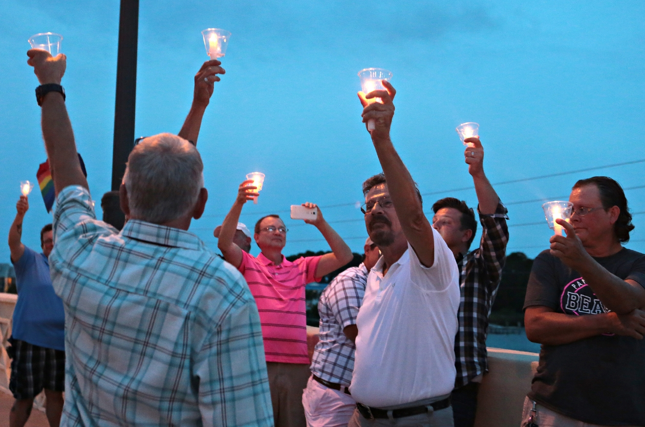 The Pride of the Panhandle holds a candlelight vigil on Sunday, June 12, 2016, in Panama City Beach, Fla., to remember the 50 killed and 53 injured in the Pulse nightclub shooting, the deadliest shooting in U.S. history. (Heather Leiphart/News Herald via AP) MANDATORY CREDIT