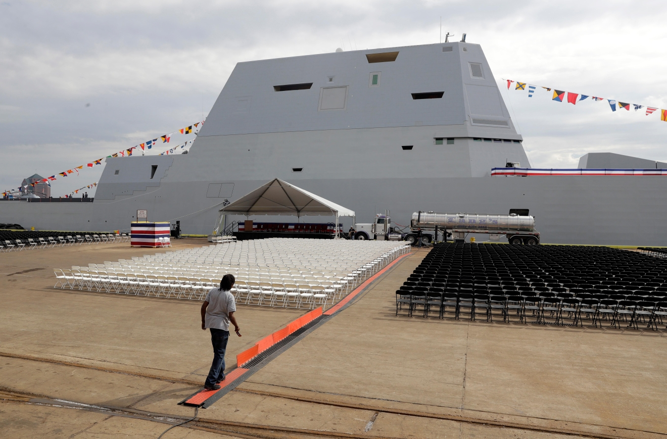 In this Oct. 13, 2016 photo, a worker prepares for a commissioning ceremony for the future USS Zumwalt, back, the U.S. Navy's newest guided-missile destroyer, in Baltimore. The destroyer's commissioning ceremony is set for Oct. 15 during the inaugural Maryland Fleet Week. (AP Photo/Patrick Semansky)