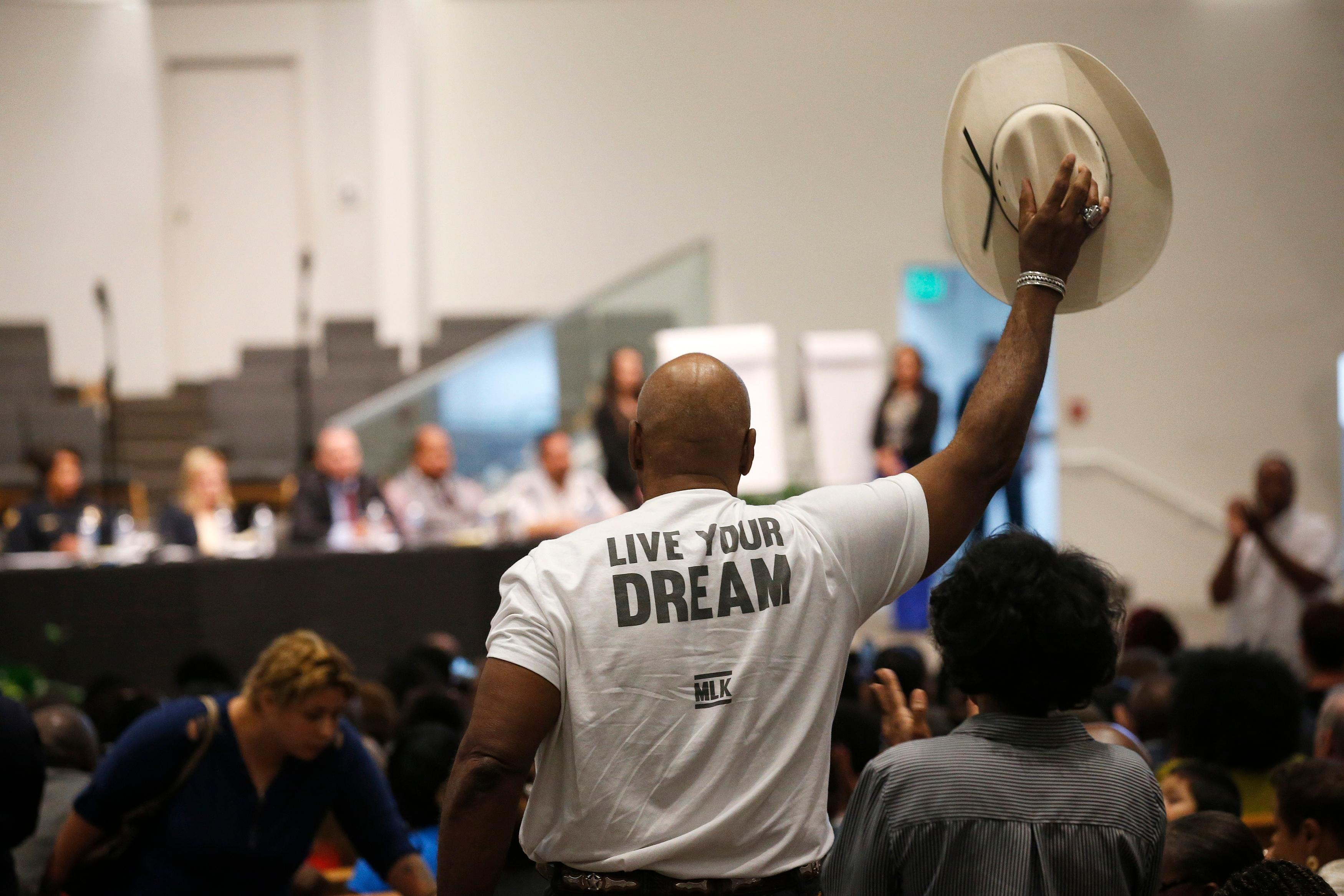 A Phoenix resident stands up to wave his cowboy hat in support of a speaker at a community meeting, Tuesday, June 18, 2019, in Phoenix. (AP Photo/Ross D. Franklin)