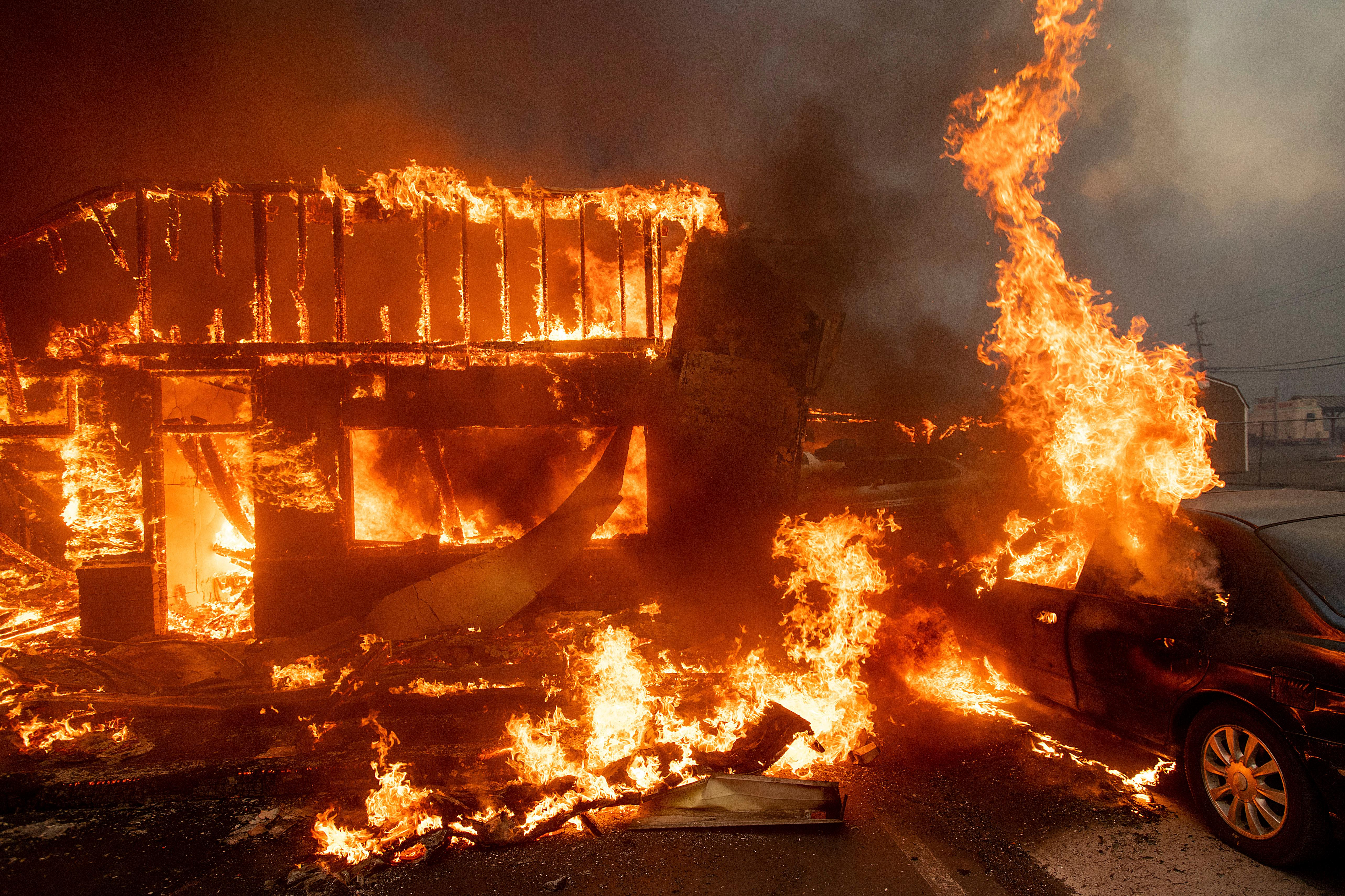 Flames consume a car and building as the Camp Fire tears through Paradise, Calif., on Thursday, Nov. 8, 2018. (AP Photo/Noah Berger)