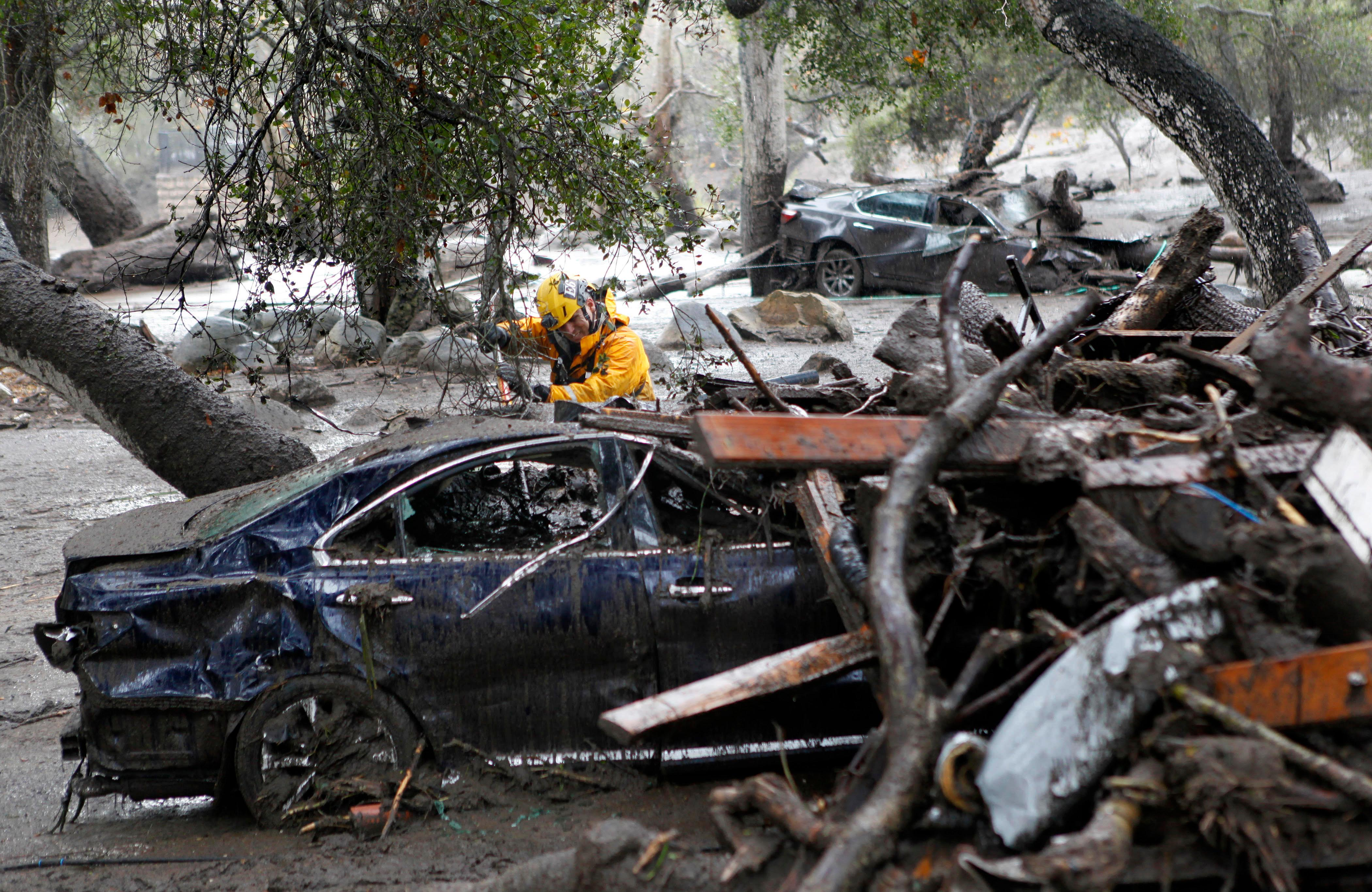 A member of the Long Beach Search and Rescue team looks for survivors in a car in Montecito, Calif., Tuesday, Jan. 9, 2018. Several homes were swept away before dawn Tuesday when mud and debris roared into neighborhoods in Montecito from hillsides stripped of vegetation during a recent wildfire. (AP Photo/Daniel Dreifuss)