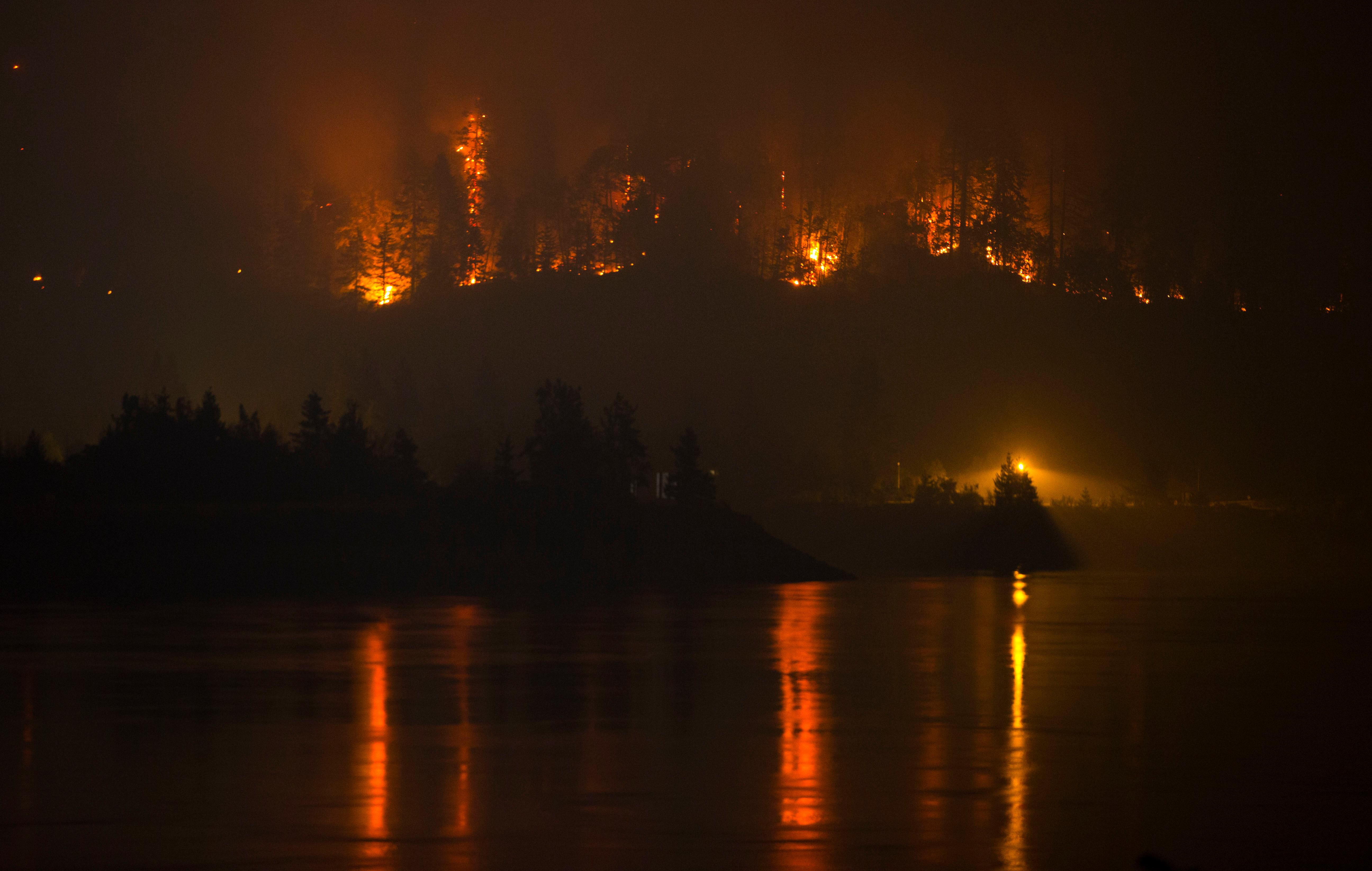 Flames are visible from the Washington side of the Columbia River above the Bonneville Dam in North Bonneville, Wash., as a wildfire moves west. The section of the Columbia River was closed after the Captain of the Port deemed it unsafe for vessels to travel the river from Reed Island to the Bonneville Dam. (Chris Pietsch/The Register-Guard via AP)