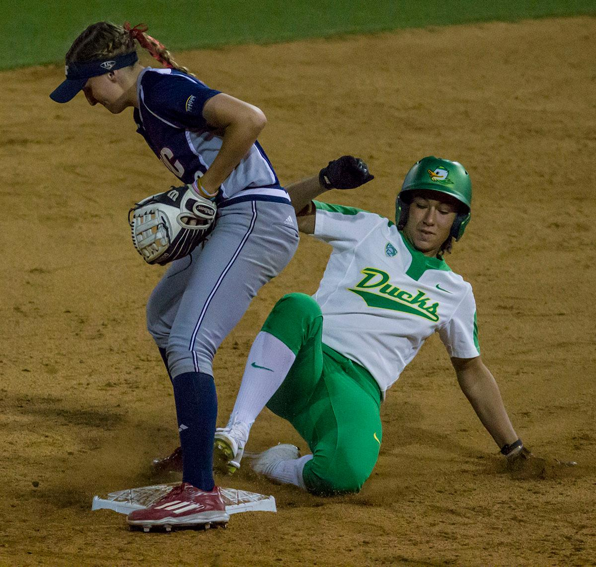 Ducks center-fielder Shannon Rhodes (#9) slides into second base. The No. 3 Oregon Ducks defeated the University of Illinois Chicago Flames 13-0 with the run-rule on Saturday night at Jane Sanders Stadium. The Ducks scored in every inning and then scored nine runs at the bottom of the fourth. The Oregon Ducks are now 22-0 in NCAA regional games. The Oregon Ducks play Wisconsin next on Saturday, May 20 at 2pm at Jane Sanders Stadium. Photo by Aaron Alter, Oregon News Lab