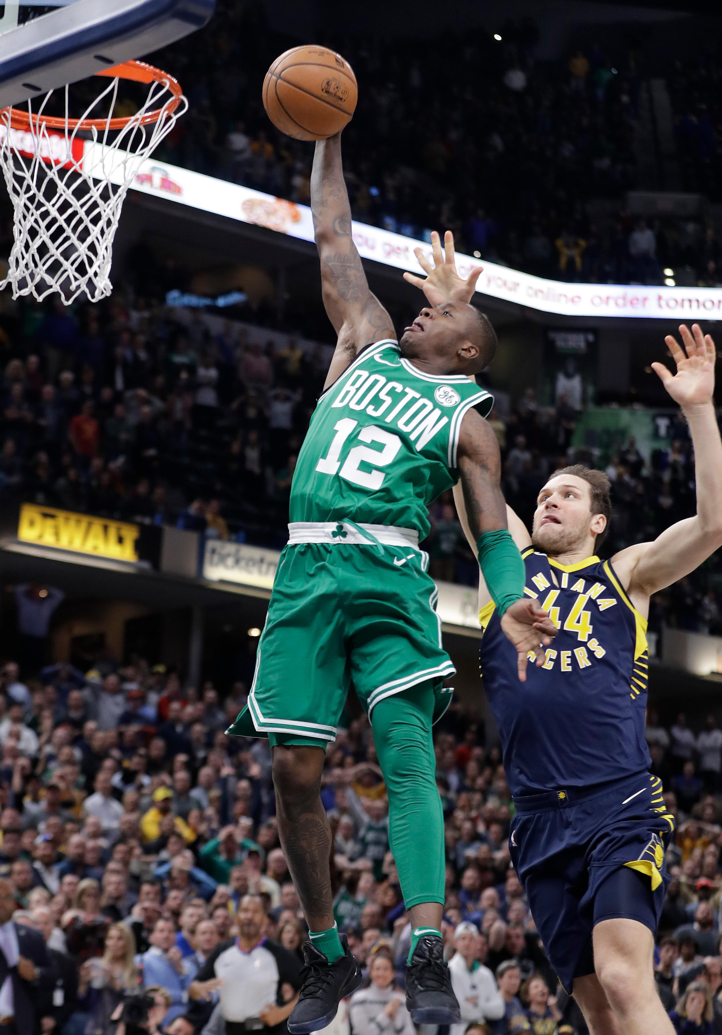 Boston Celtics' Terry Rozier (12) goes up for the game winning dunk against Indiana Pacers' Bojan Bogdanovic during the second half of an NBA basketball game, Monday, Dec. 18, 2017, in Indianapolis. Boston won 112-111. (AP Photo/Darron Cummings)