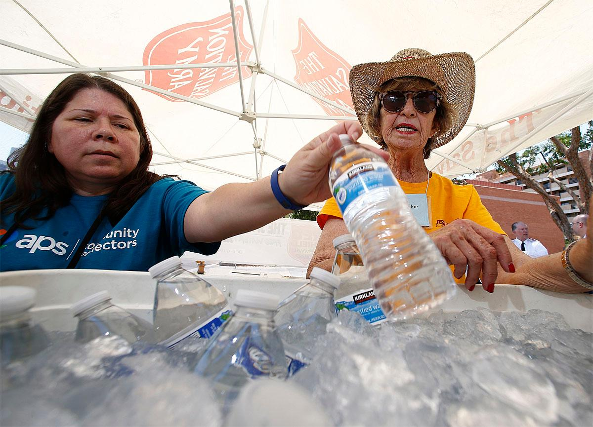 Salvation Army volunteers Evangeline Ford, left, and Jackie Rifkin, right, restock a cooler with bottles of water at a hydration station for people as they try to keep hydrated and stay cool as temperatures climb to near-record highs, Monday, June 19, 2017, in Phoenix. (AP Photo/Ross D. Franklin)