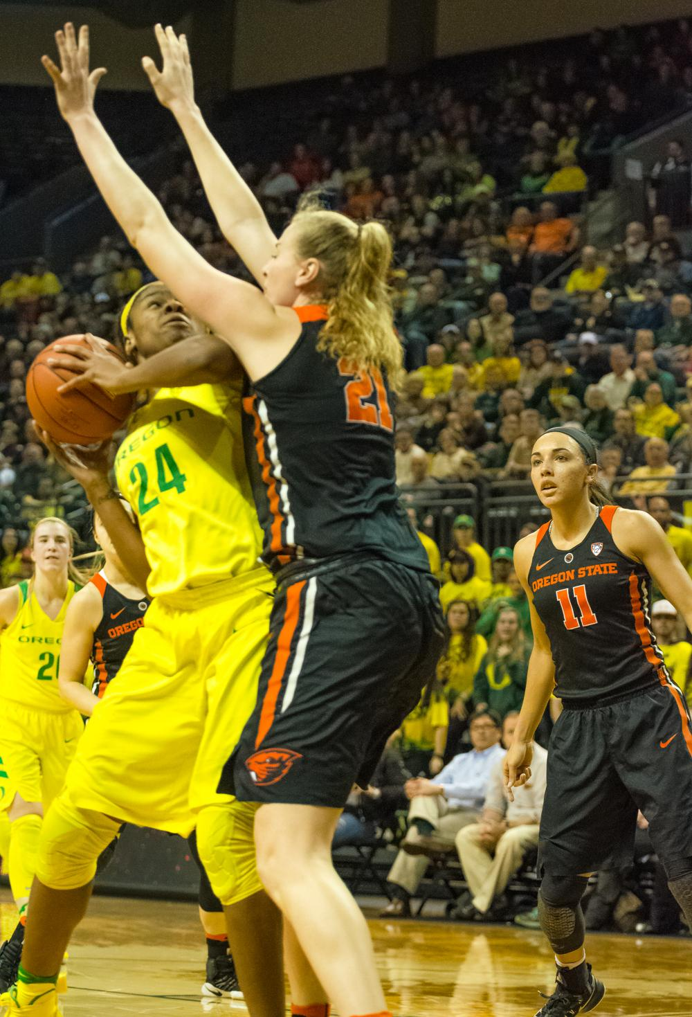 Oregon Ducks Forward Ruthy Hebard (#24) fights through the arms of Oregon State Center Marie Gulich (#21). Oregon Ducks lost 40-43 to Oregon State Beavers in a tightly matched fourth quarter. Photo by Jonathan Booker, Oregon News Lab
